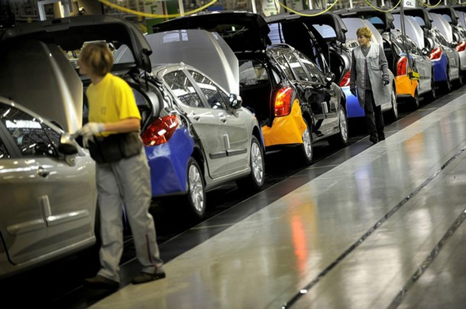 Employees working on an assembly line of the PSA Peugeot Citroen car factory in Sohaux, France, Sept. 11, 2008. (AFP Photo)