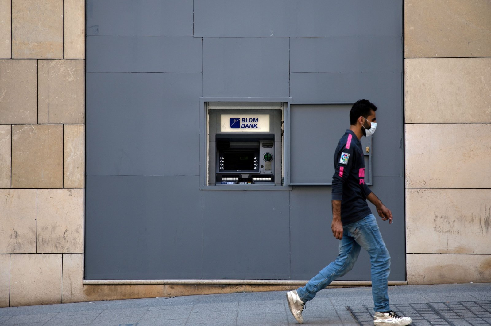A man wearing a face mask walks past a fortified Blom Bank ATM machine, in Beirut, Lebanon, Aug. 21, 2020. (Rueters Photo)