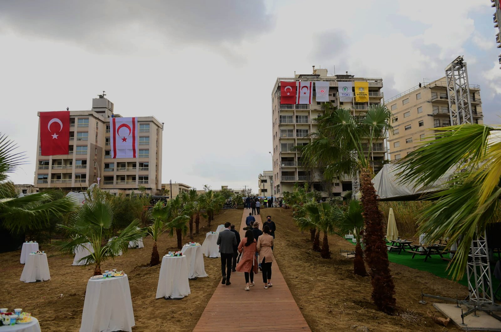 People walk in front of abandoned buildings adorned with Turkish and Turkish Cyprus flags before Turkish President Recep Tayyip Erdoğan inspects the newly opened beachfront of Varosha, Turkish Cyprus, Nov. 15, 2020. (AP Photo)