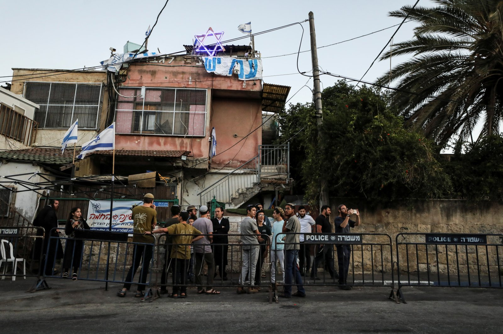 Orthodox Jewish youth stand next to an Israeli police barricade in Sheikh Jarrah neighborhood, where Palestinian families face possible eviction after an Israeli court accepted Jewish settler land claims, in East Jerusalem, occupied Palestine, June 6, 2021. (Reuters Photo)