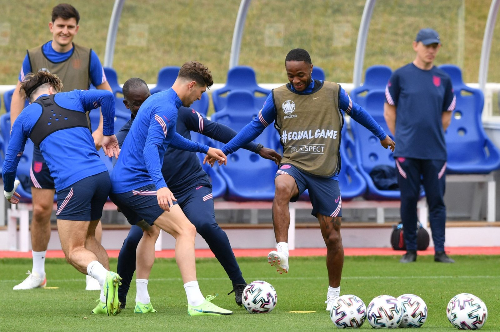 England forward Raheem Sterling (R) and England's defender John Stones (C) fight for a ball with teammates during a training session at the Tottenham Hotspur training ground, London, England, June 17, 2021. (AFP Photo)