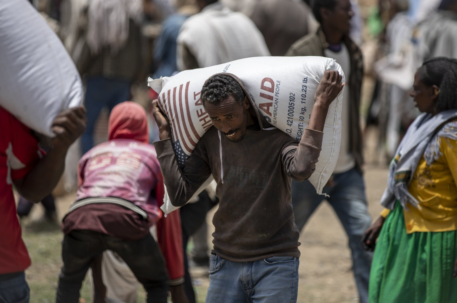 An Ethiopian man carries a sack of wheat on his shoulders to be distributed by the Relief Society of Tigray in the town of Agula, Tigray region, northern Ethiopia, May 8, 2021. (AP Photo)