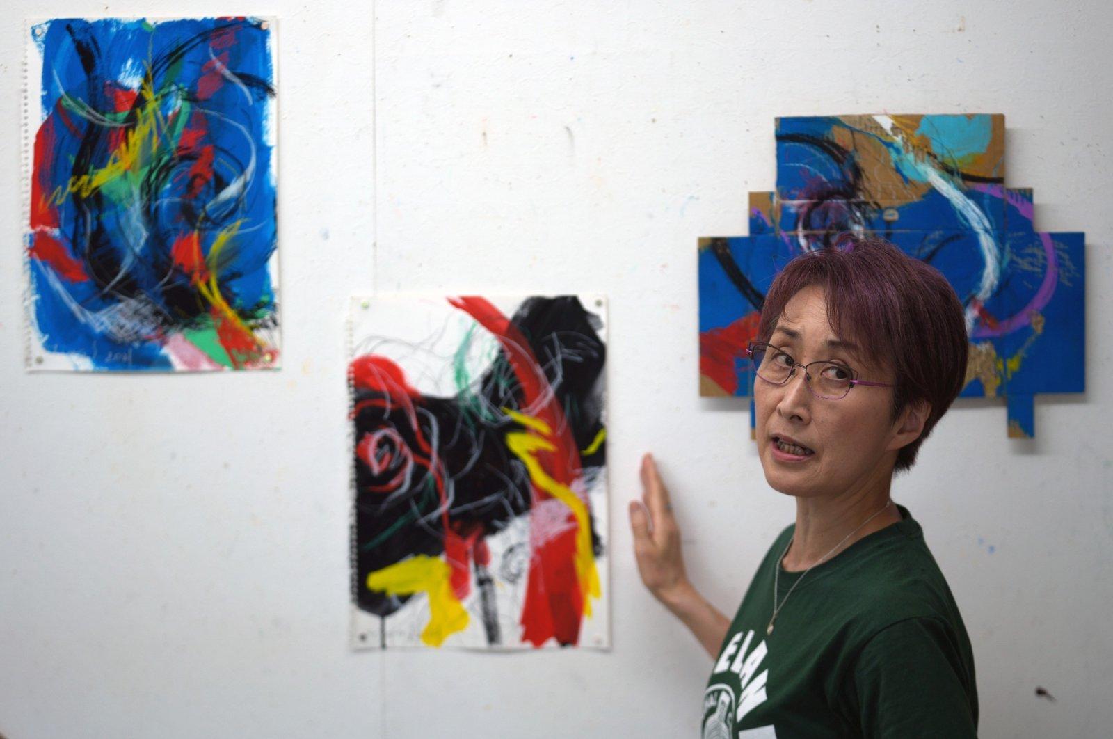 """Japanese artist Miwako Sakauchi speaks about her artwork for the art exhibition """"Declaration of the end of Olympic games"""" in Chiba near Tokyo, Japan, June 10, 2021. (AP Photo)"""