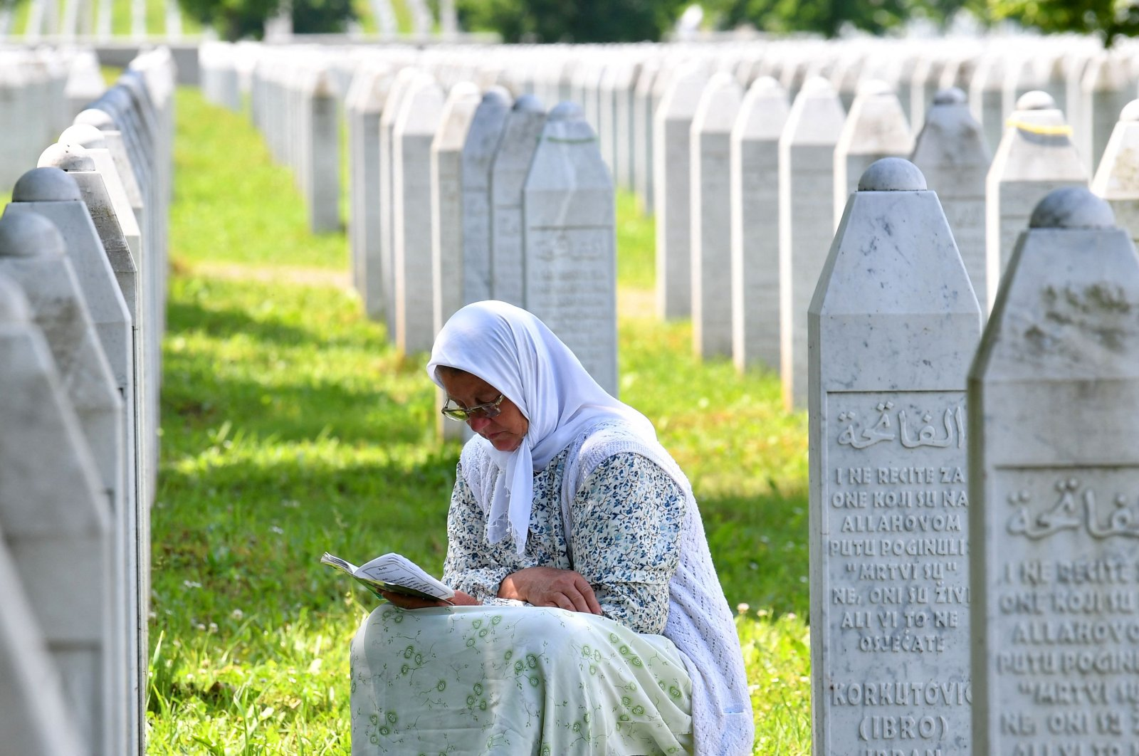 A Bosnian Muslim woman reads from a book of prayers among gravestones of her relatives who fell as victims of the Srebrenica 1995 massacre at Srebrenica Memorial Cemetery, in Potocari, Bosnia and Herzegovina, June 8, 2021 (AFP Photo)