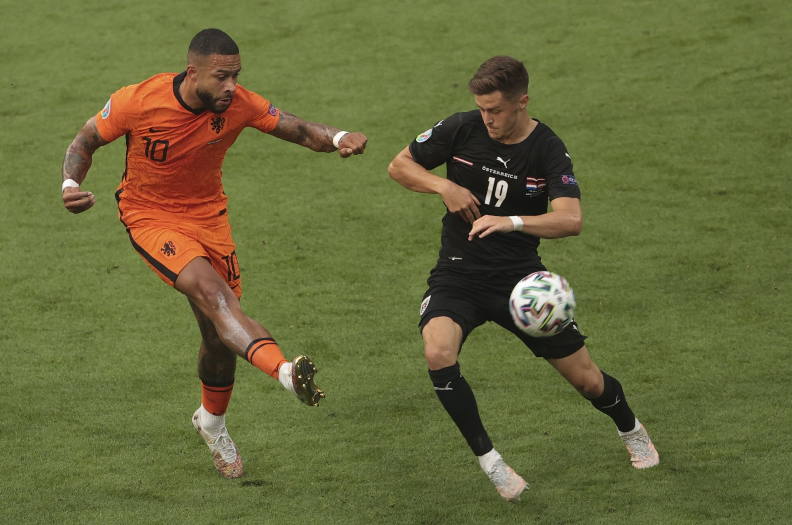 Dutch player Memphis Depay (10) in action with Austria's Christoph Baumgartner (19) during the EURO 2020 match on June 17, 2021 (AA Photo)