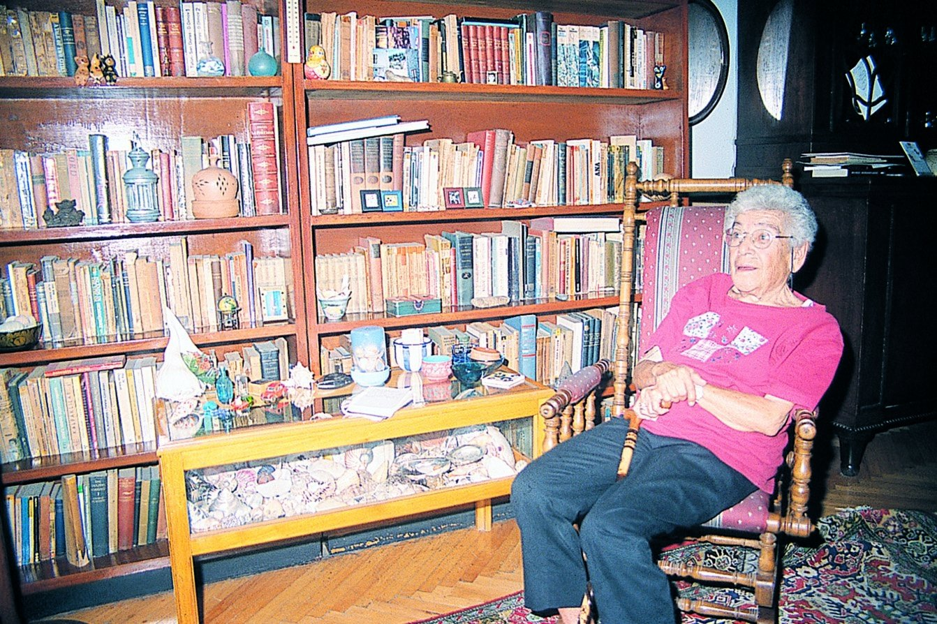 Mina Urgan sits in front of a bookcase in her house. (Archive Photo)