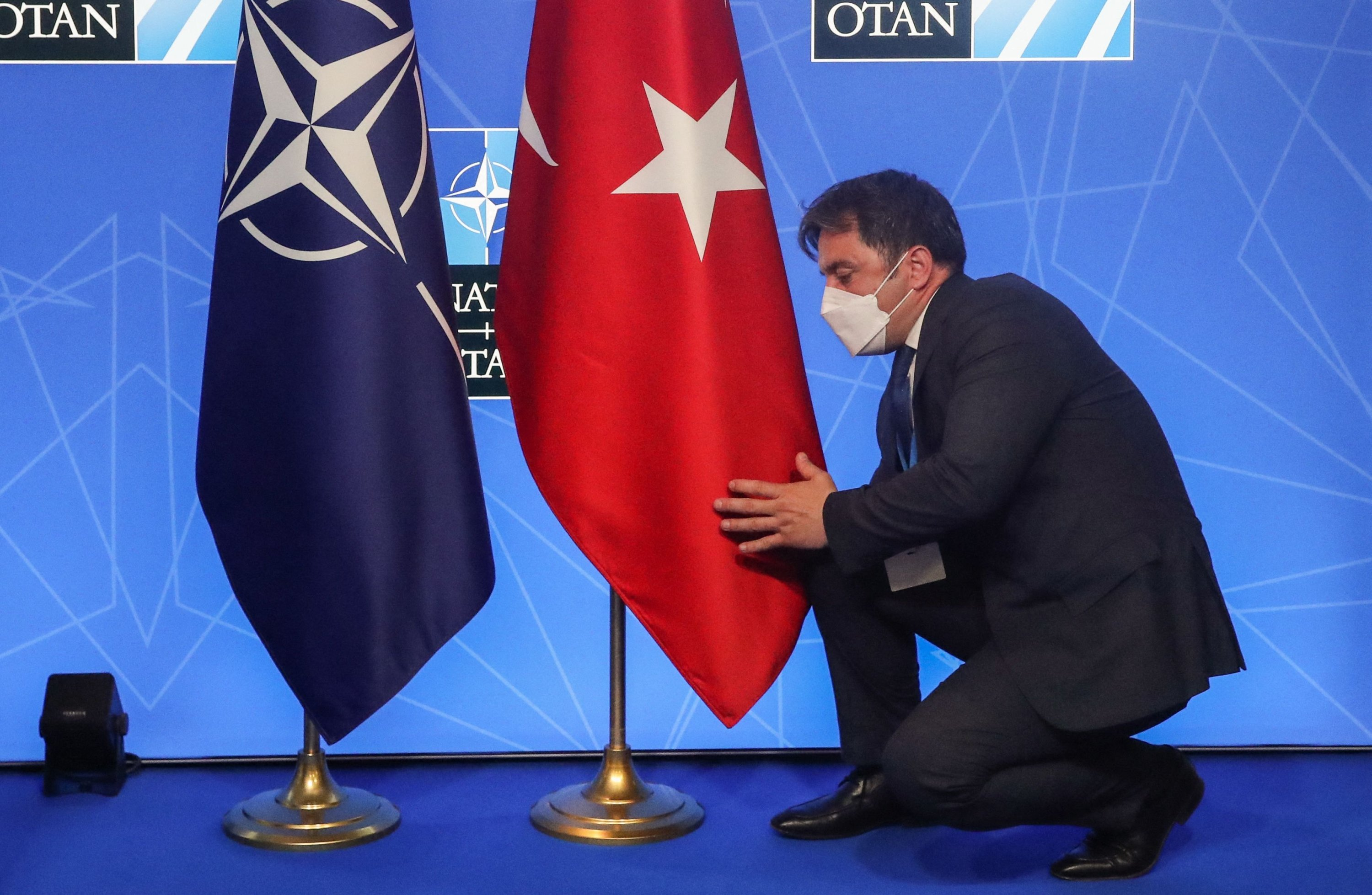 An official adjusts the Turkish flag before a news conference by President Recep Tayyip Erdoğan during the NATO summit, Brussels, Belgium, June 14, 2021. (AFP Photo)