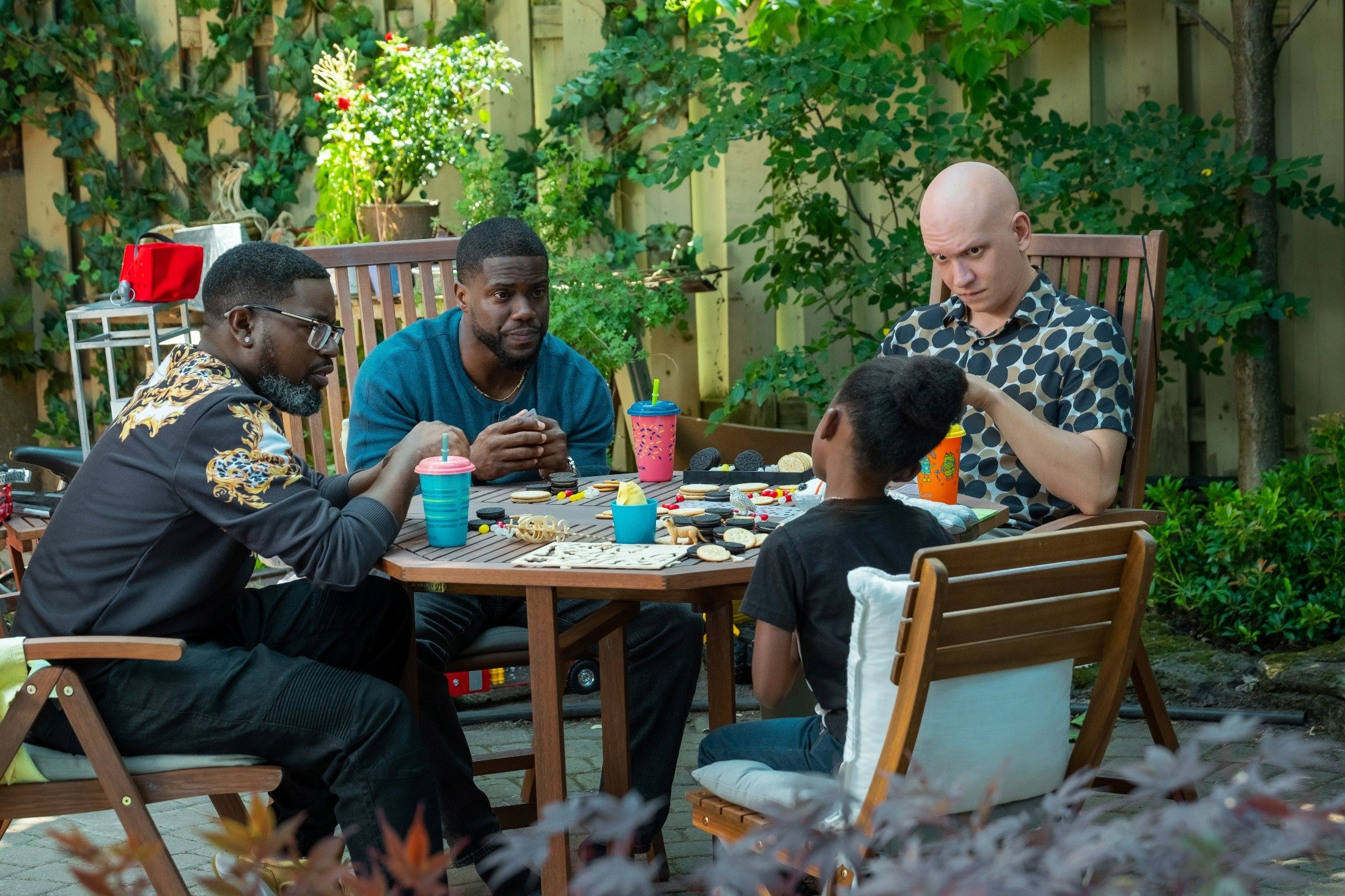 Lil Rey Howery (L), Kevin Hart (C-L), Melody Hurd (C-R) and Anthony Carrigan sit around a table, in a scene from the movie 'Fatherhood.' (Netflix via AP)