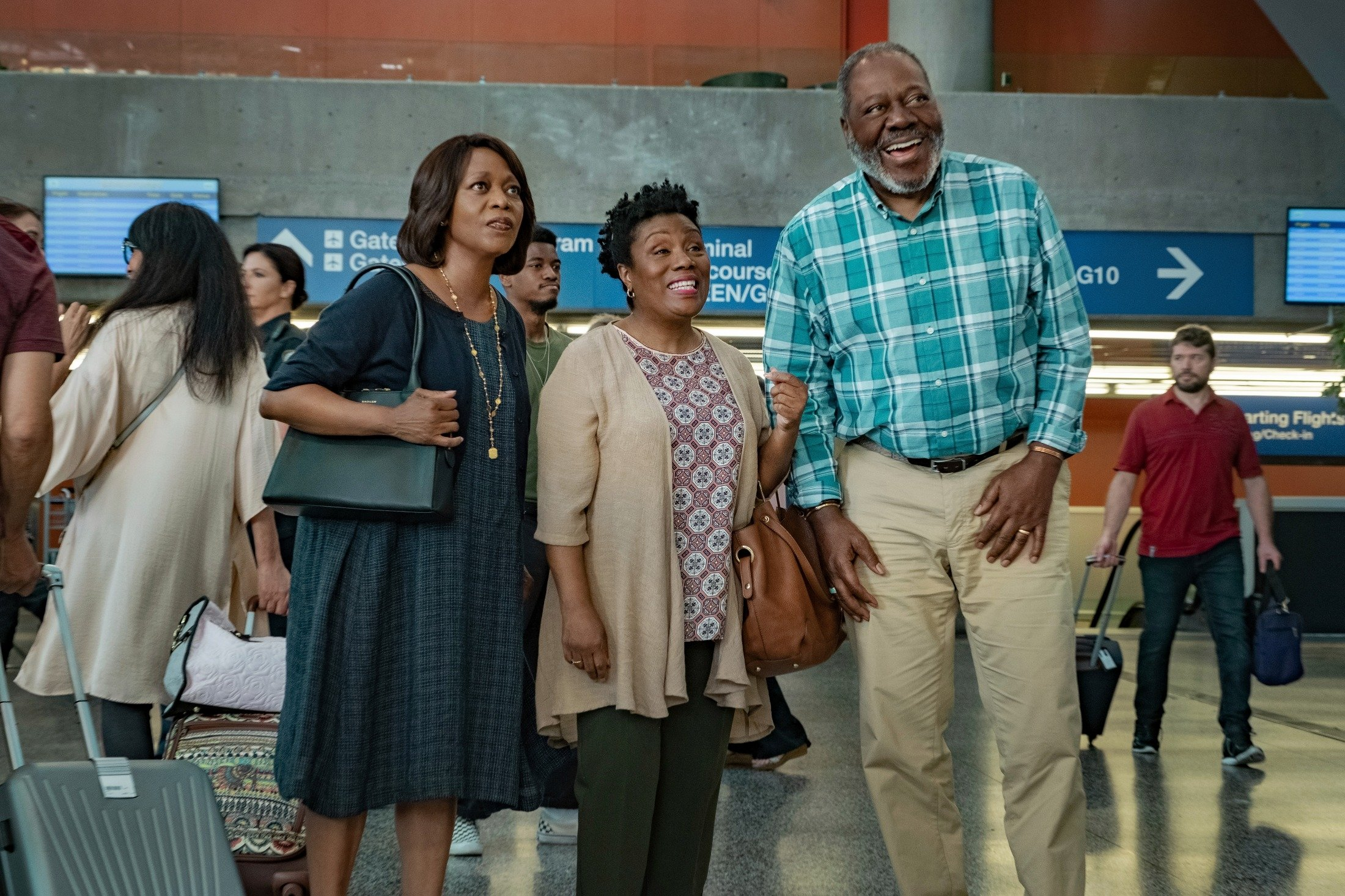Alfre Woodard (L), Thedra Porter (C) and Frankie Faison wait for someone at an airport, in a scene from the movie 'Fatherhood.' (Netflix via AP)