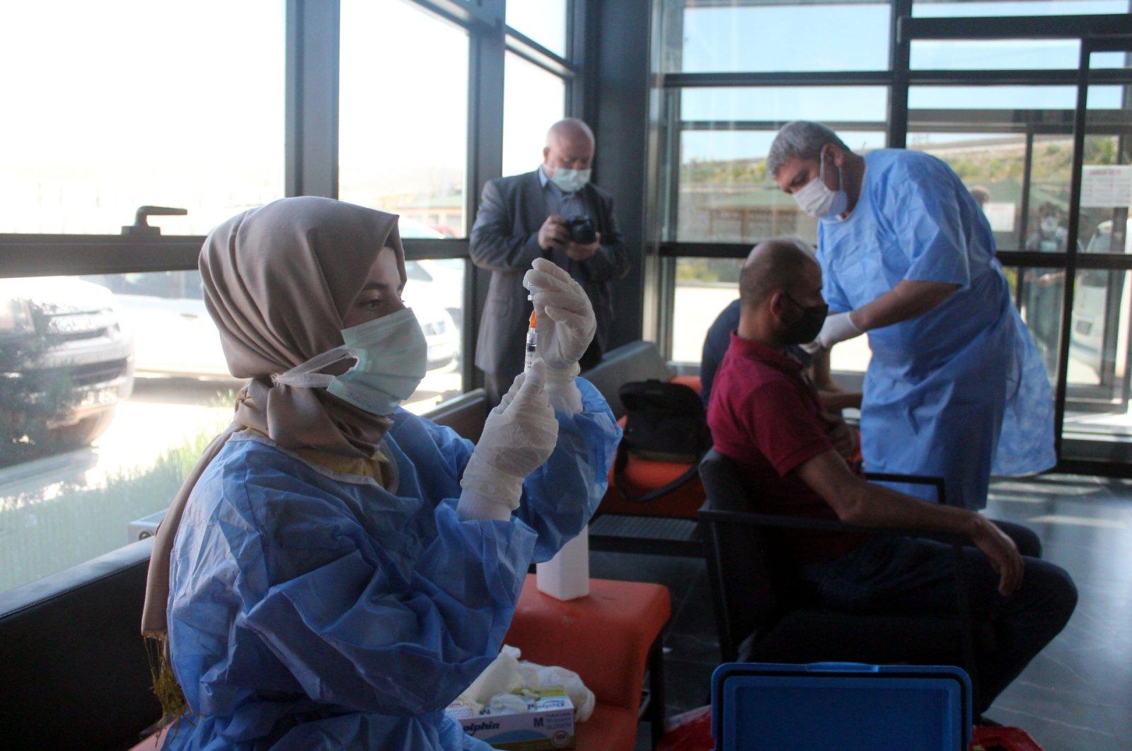 A nurse prepares a vaccine, while a man has his COVID-19 jab, in Bayburt, northeastern Turkey, June 18, 2021. (AA PHOTO)