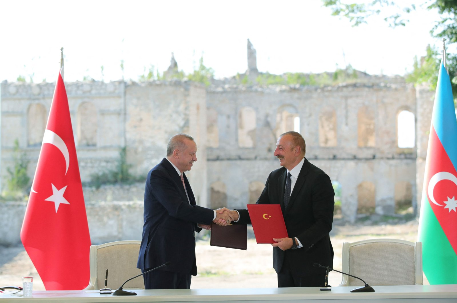 Turkish President Recep Tayyip Erdoğan (L) and Azerbaijani President Ilham Aliyev (R) shake hands after signing the Shusha Declaration in Shusha, Nagorno-Karabakh, Azerbaijan, June 15, 2021. (Turkish Presidential Press Office via AFP)