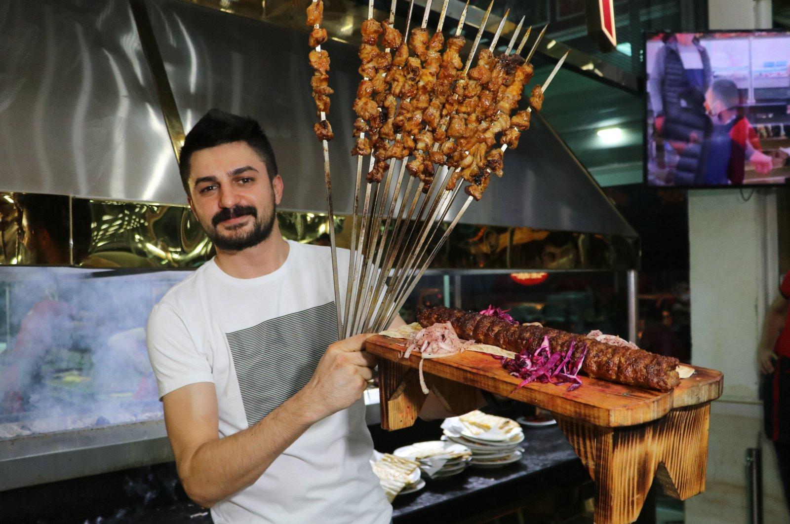 Uğur Aydın poses with various kebabs in his restaurant in Adana, Turkey, June 17, 2021. (IHA Photo)