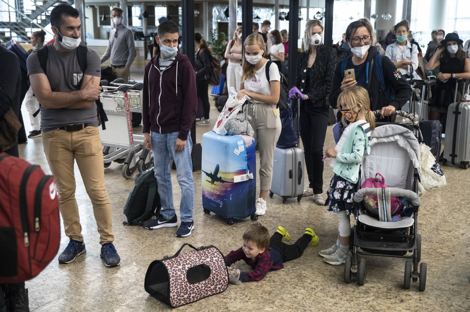 A child plays with a pet as people wait in line to check-in at Sheremetyevo International Airport, outside Moscow, Russia, Aug. 1, 2020. (AP File Photo)
