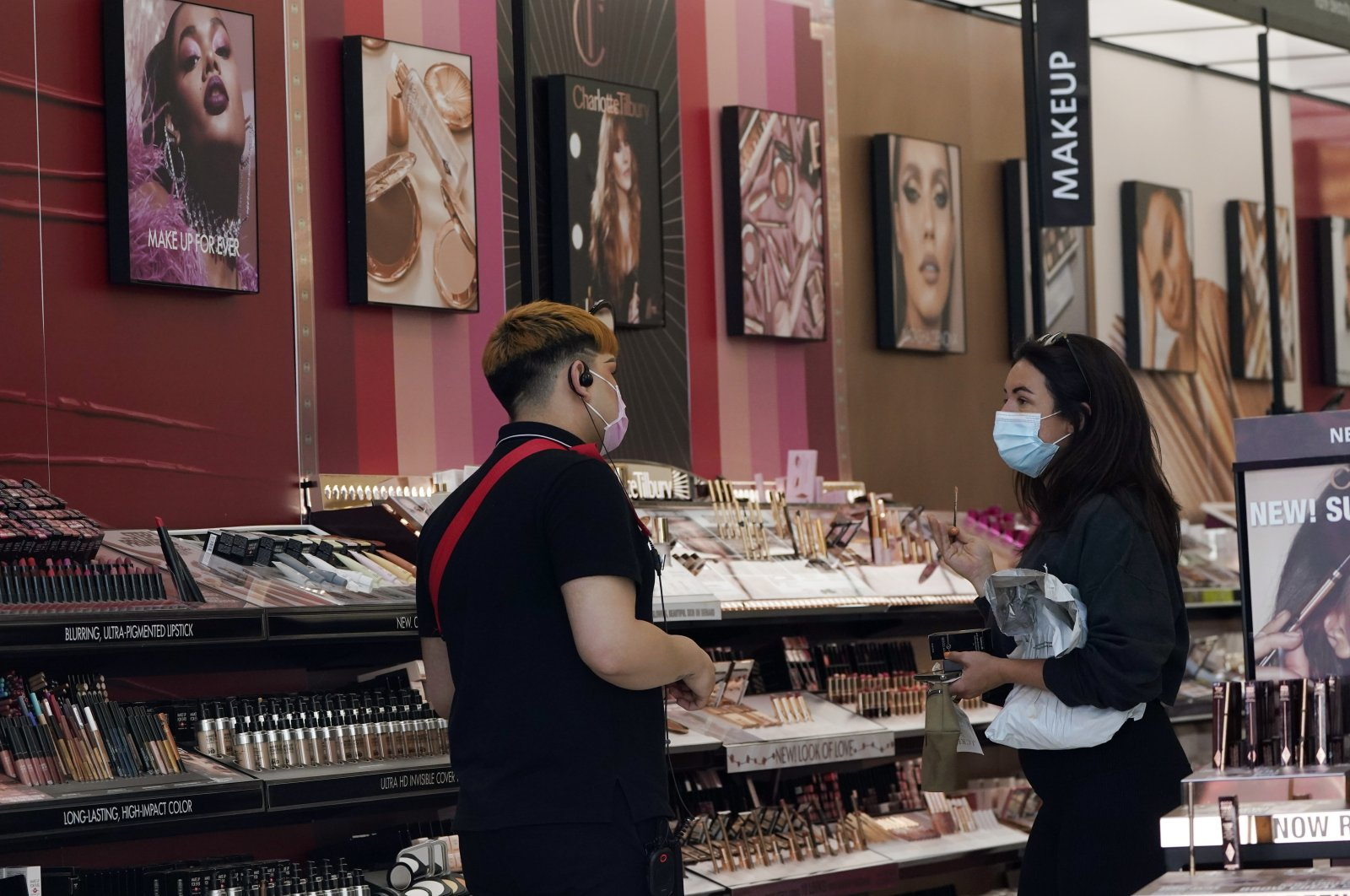 A worker (L), tends to a customer at a cosmetics shop amid the COVID-19 pandemic in Los Angeles, California, U.S., May 20, 2021. (AP Photo)