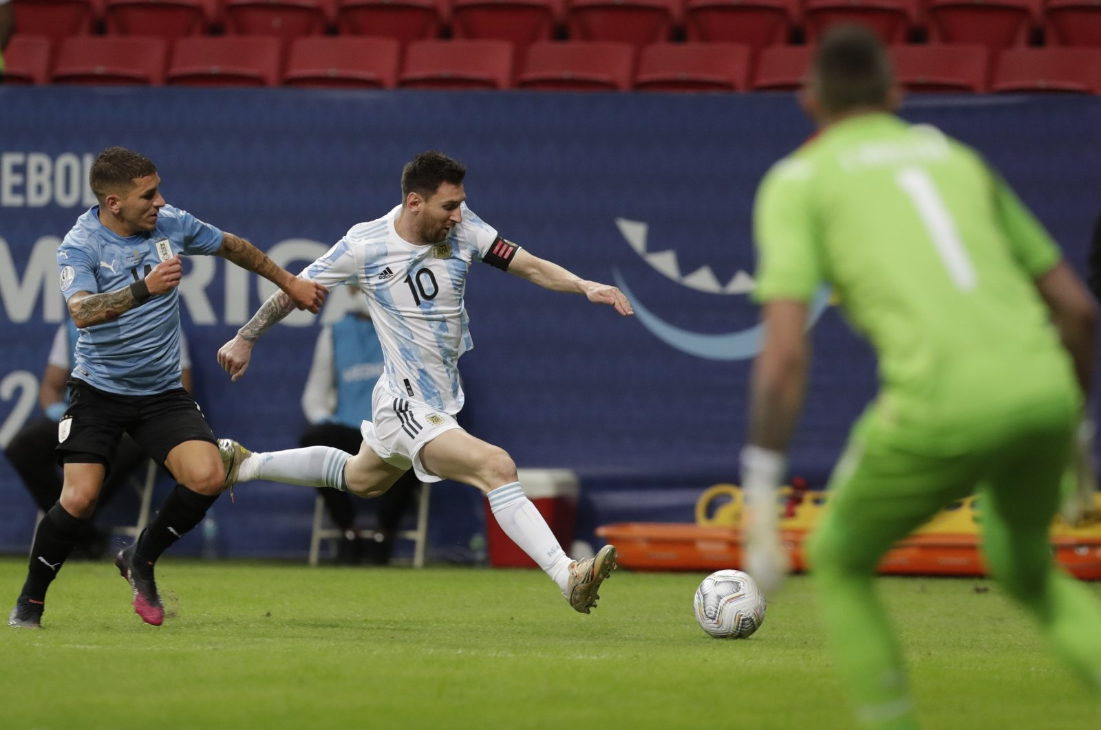 Uruguay's Lucas Torreira (L) tries to prevent Argentina's Lionel Messi (C) from dribbling past during a Copa America football match at Mané Garrincha Stadium in Brasilia, Brazil, June 18, 2021. (AP Photo)