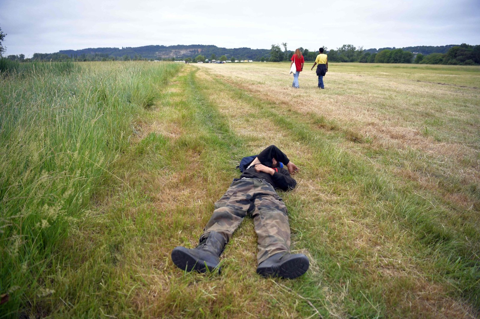 Two participants of an illegal rave party cross a field while another lies on the ground, in Redon, northwestern France, June 19, 2021. (AFP Photo)