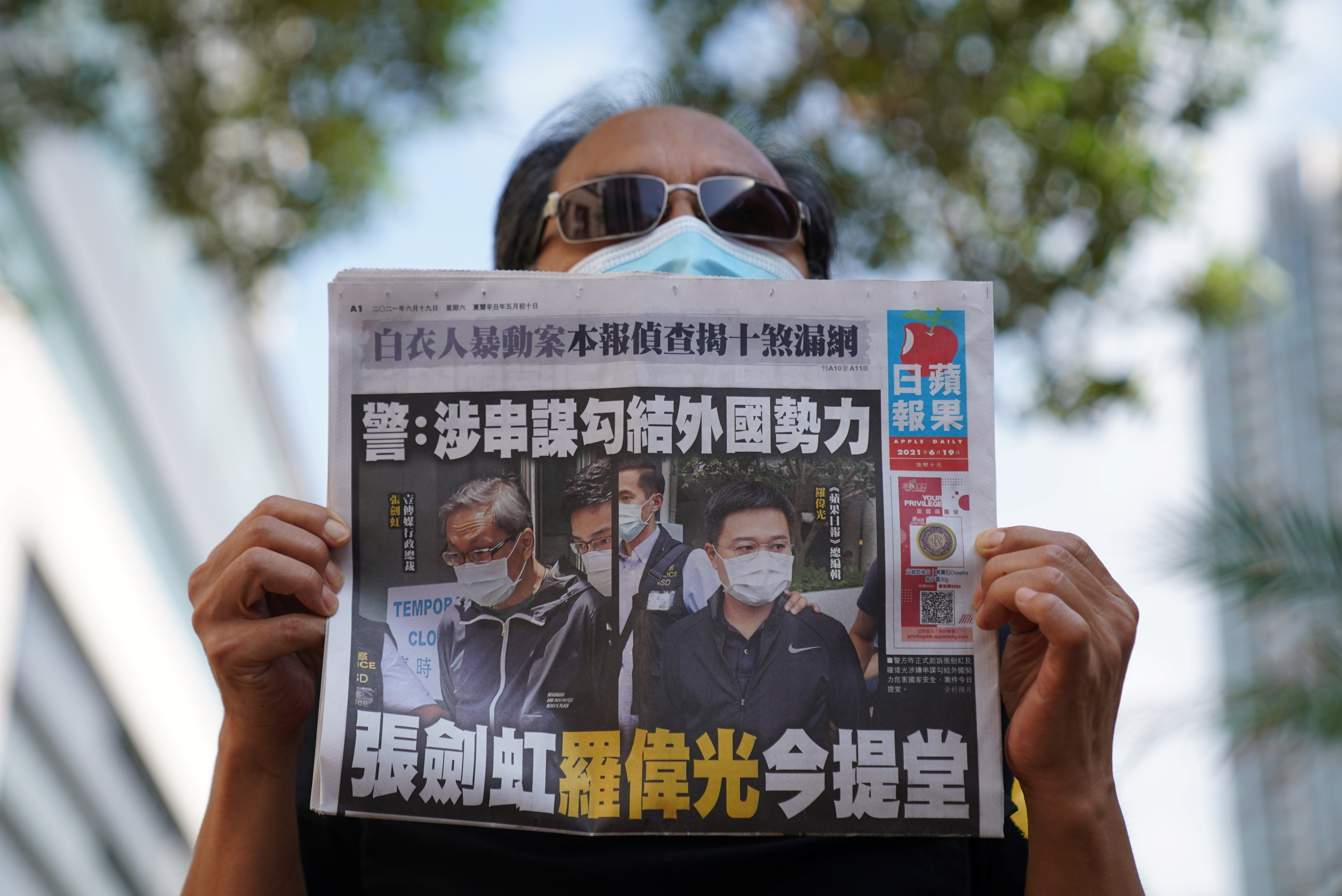 A supporter holds a copy of the anti-Beijing Apple Daily newspaper during a court hearing after police charged two executives of the newspaper under a national security law, outside West Magistrates' Courts in Hong Kong, China, June 19, 2021. (Reuters Photo)