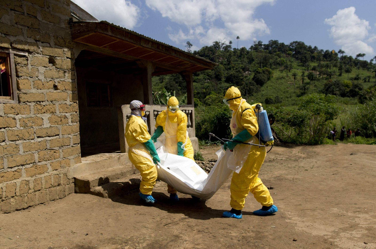 Guinean Red Cross workers wearing protective suits carry the corpse of a victim of Ebola in Macenta, Guinea, Nov. 21, 2014. (AFP Photo)