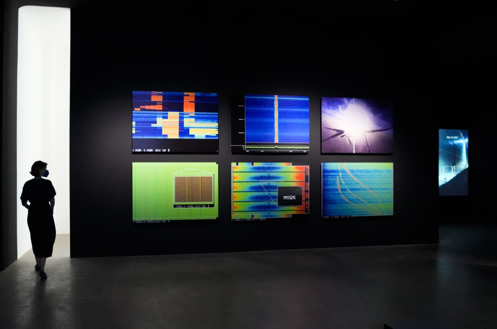 """A woman walks through an exhibition by American artist and filmmaker Laura Poitras, near the art work """"Anarchist"""" by Laura Poitras in collaboration with Henrik Moltke, at the N.K.B. gallery in Berlin, Germany, June 18, 2021. (AP Photo)"""