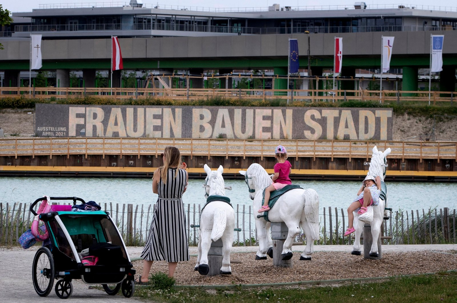 """Children play in a playground facing large panels proclaiming the slogan """"Women build the city"""" next to some of the building sites that will eventually contain 12,000 new housing units, at Vienna's suburb Seestadt, Austria, June 8, 2021. (AFP Photo)"""