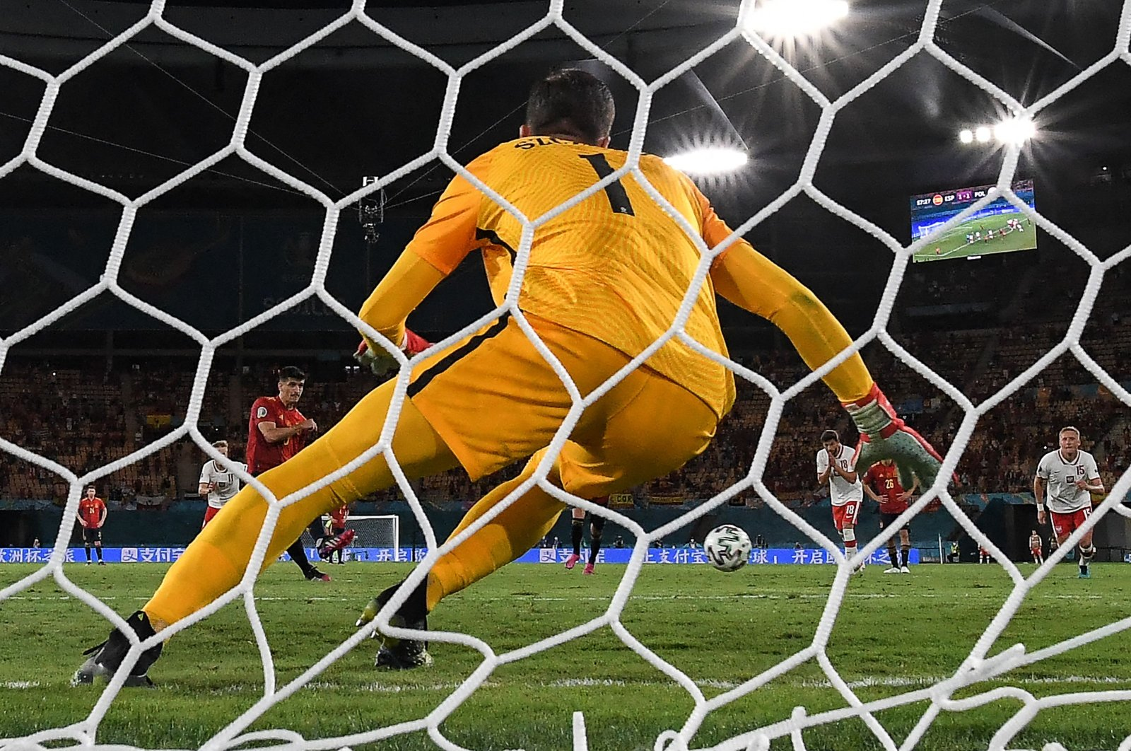 Spain's forward Gerard (L) fails to score a penalty past Poland's goalkeeper Wojciech Szczesny during the UEFA EURO 2020 Group E football match between Spain and Poland at La Cartuja Stadium in Seville, Spain, June 19, 2021. (AFP Photo)