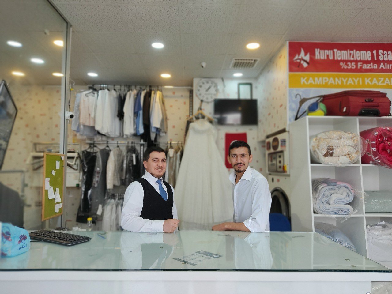 Brothers Mohammed and Ahmed Mulla stand behind the counter at their dry cleaning center in the capital Ankara, Turkey, June 19, 2021. (AA Photo)