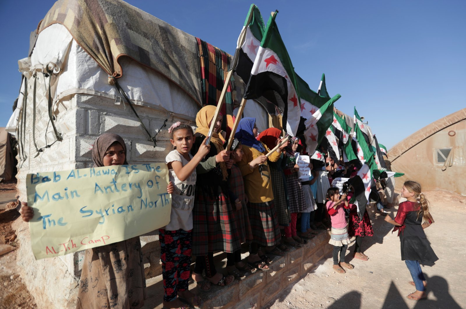 An internally displaced Syrian girl holds a sign during a protest against the closure of Bab al-Hawa crossing in the opposition-held Idlib, northwestern Syria, June 7, 2021. (REUTERS Photo)