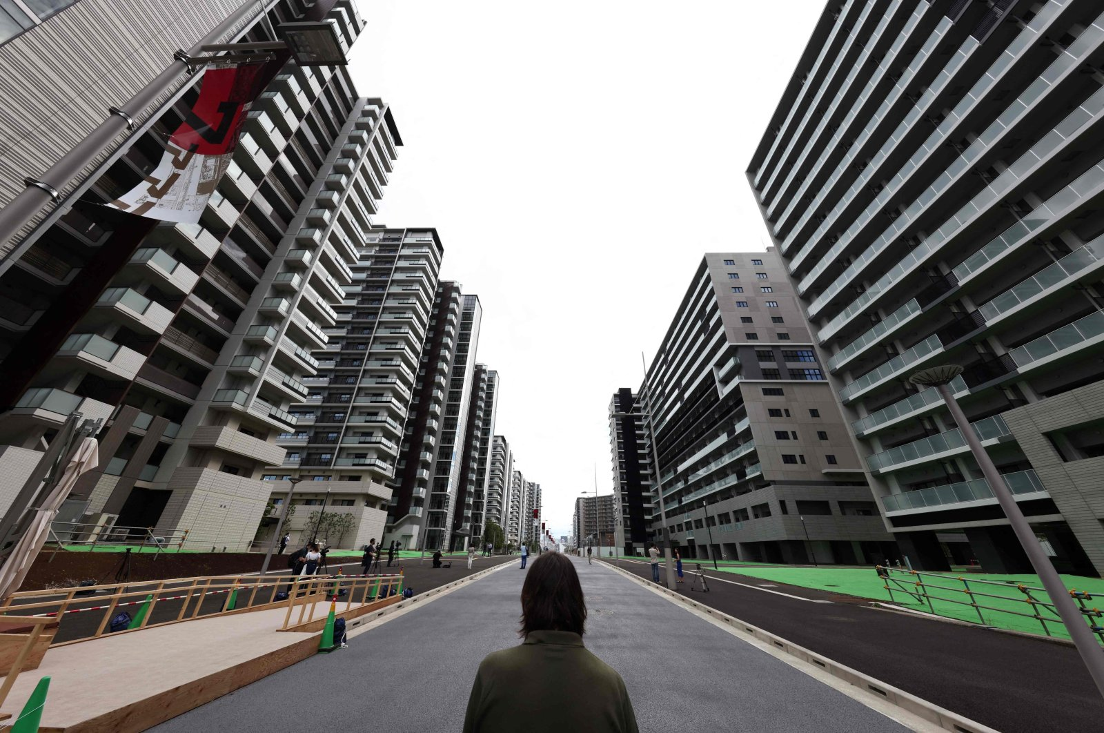 A reporter looks at the buildings that will host the athletes during the 2020 Tokyo Olympic Games, during a media tour of the Olympic Village, Tokyo, Japan, June 20, 2021. (AFP Photo)