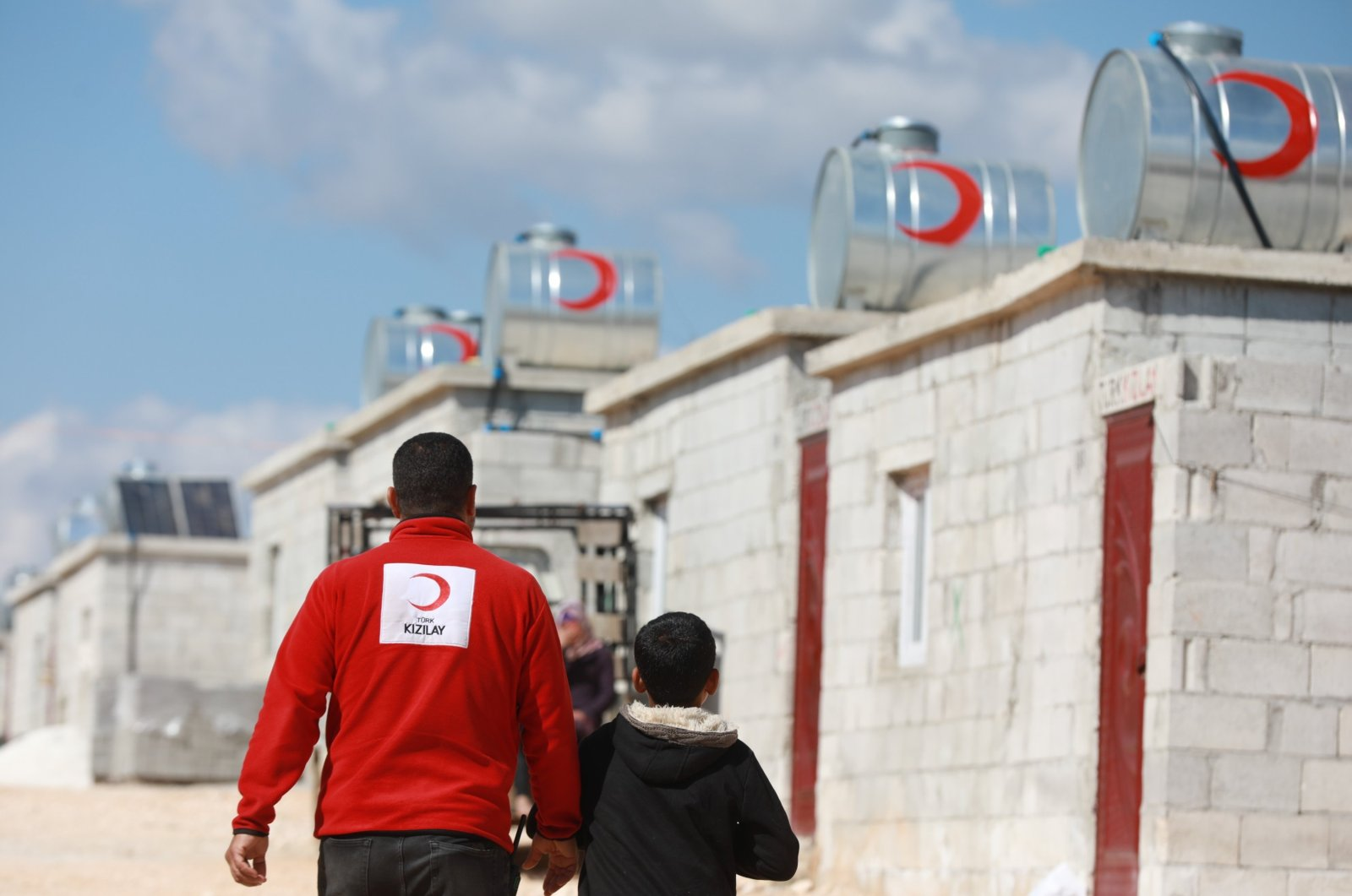 A Turkish Red Crescent (Kızılay) volunteer walks with a child near houses built by Kızılay for displaced Syrians in Sarmada, Idlib province, Syria, April 3, 2021. (AA Photo)