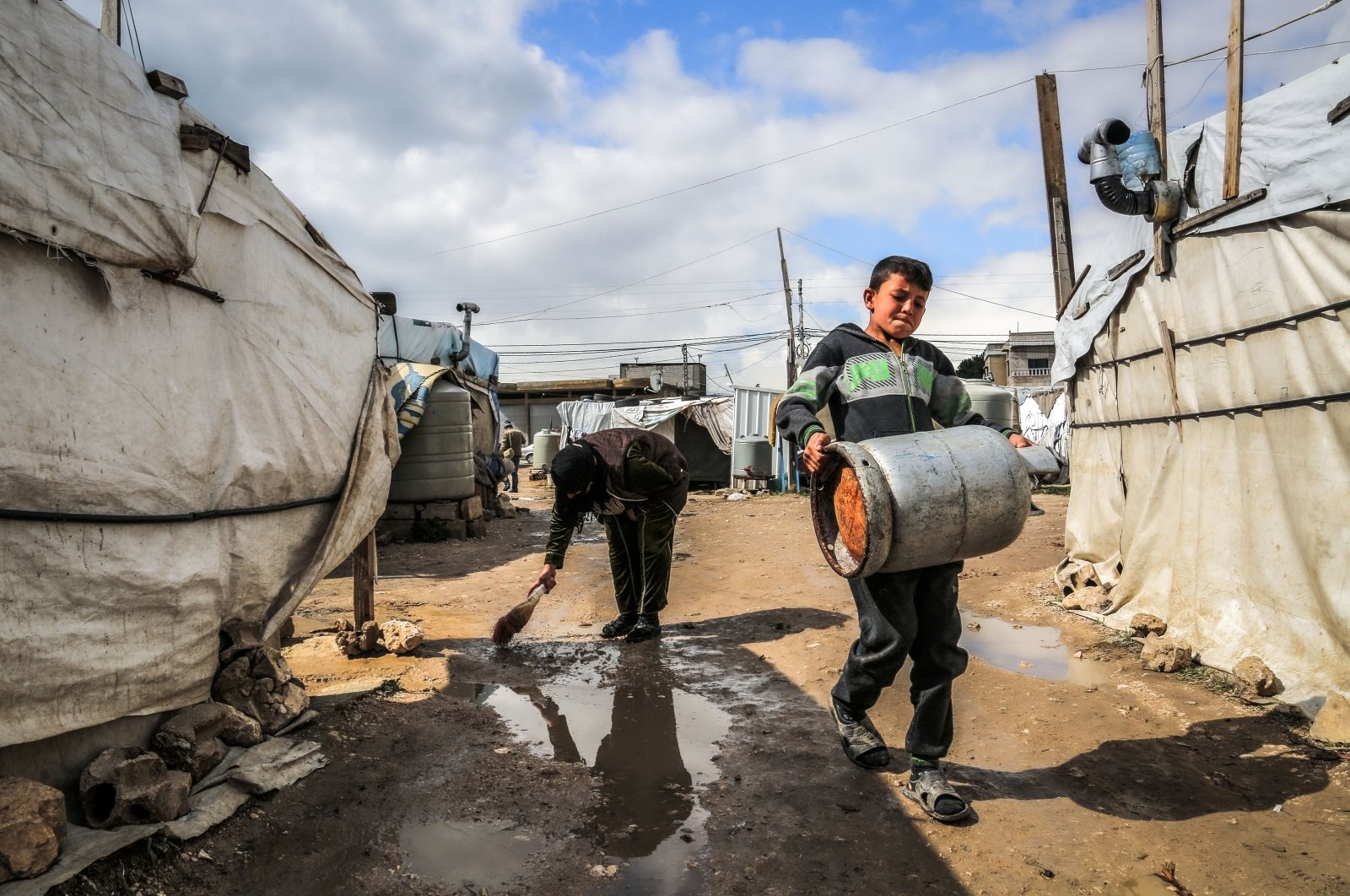 A Syrian refugee clears rainwater outside her tent following heavy rain, at Marj Syrian refugee camp in Lebanon's Bekaa valley, Feb. 20, 2021 (Getty Images)