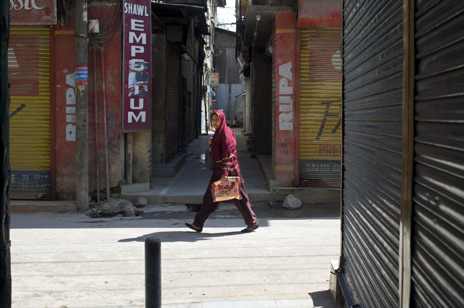 A Kashmiri Muslim woman walks past a closed market during a strike in Srinagar, Indian-administrated Kashmir, India, April 11, 2015. (AP Photo)