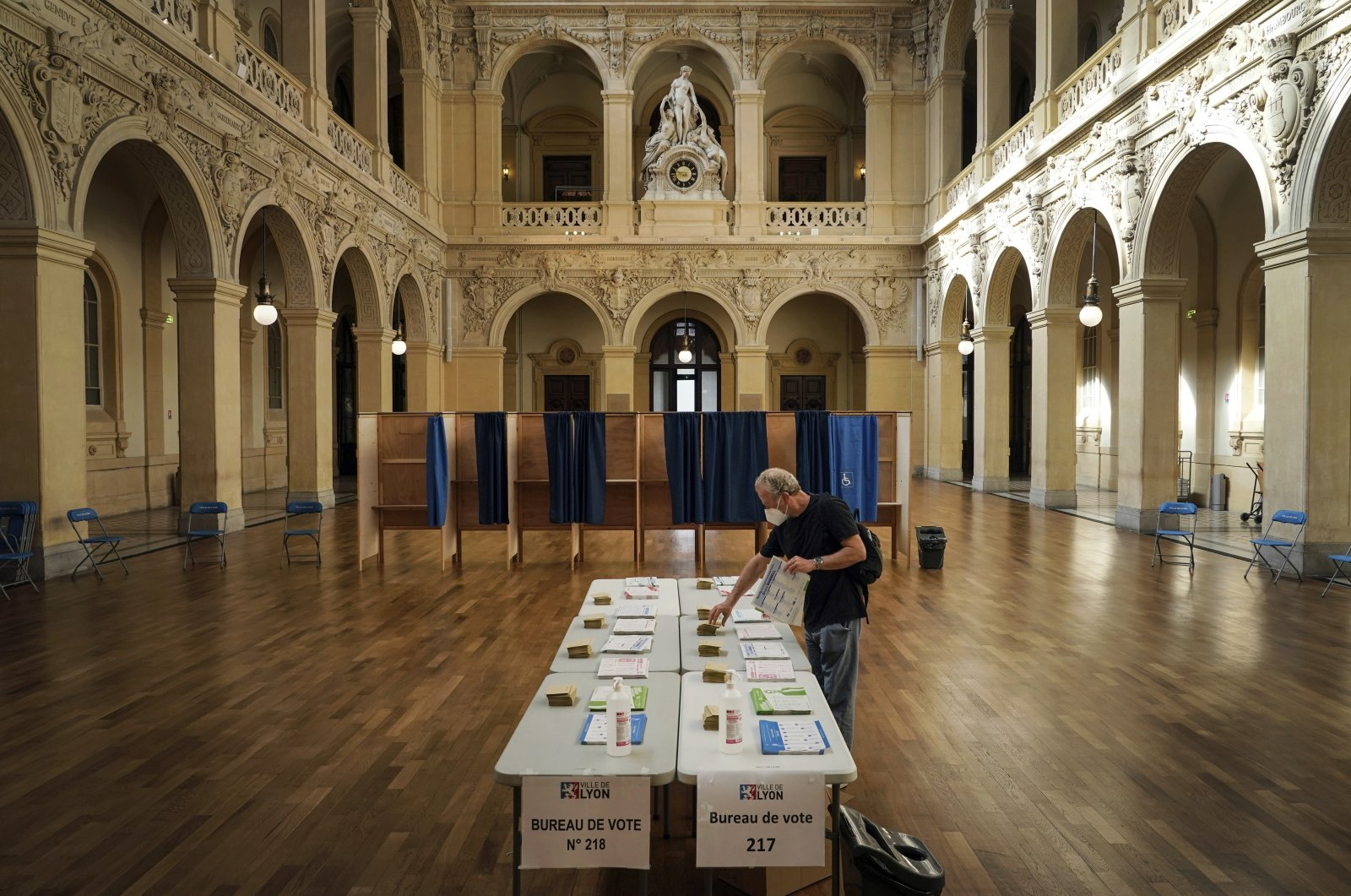 A voter picks up ballots before voting for the regional elections in Lyon, central France, June 20, 2021. (AP Photo)