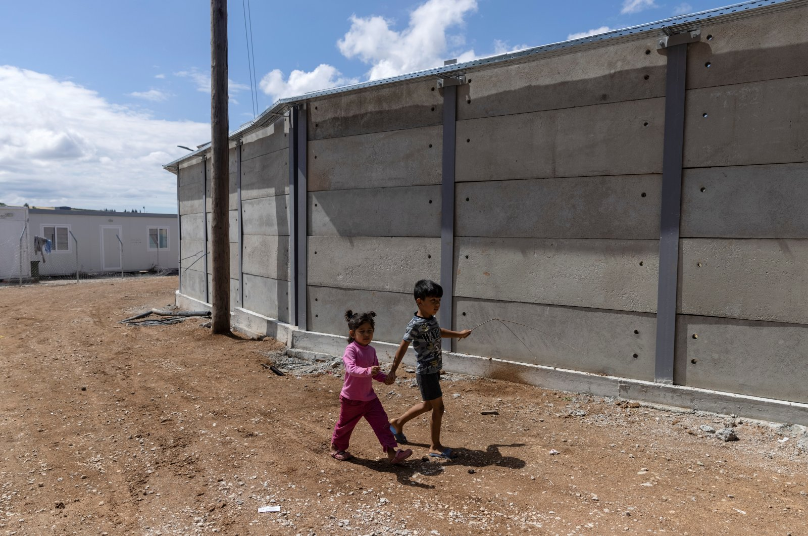 Children walk next to a newly built concrete wall inside the Ritsona camp for refugees and migrants, in Greece, June 15, 2021. (Reuters Photo)
