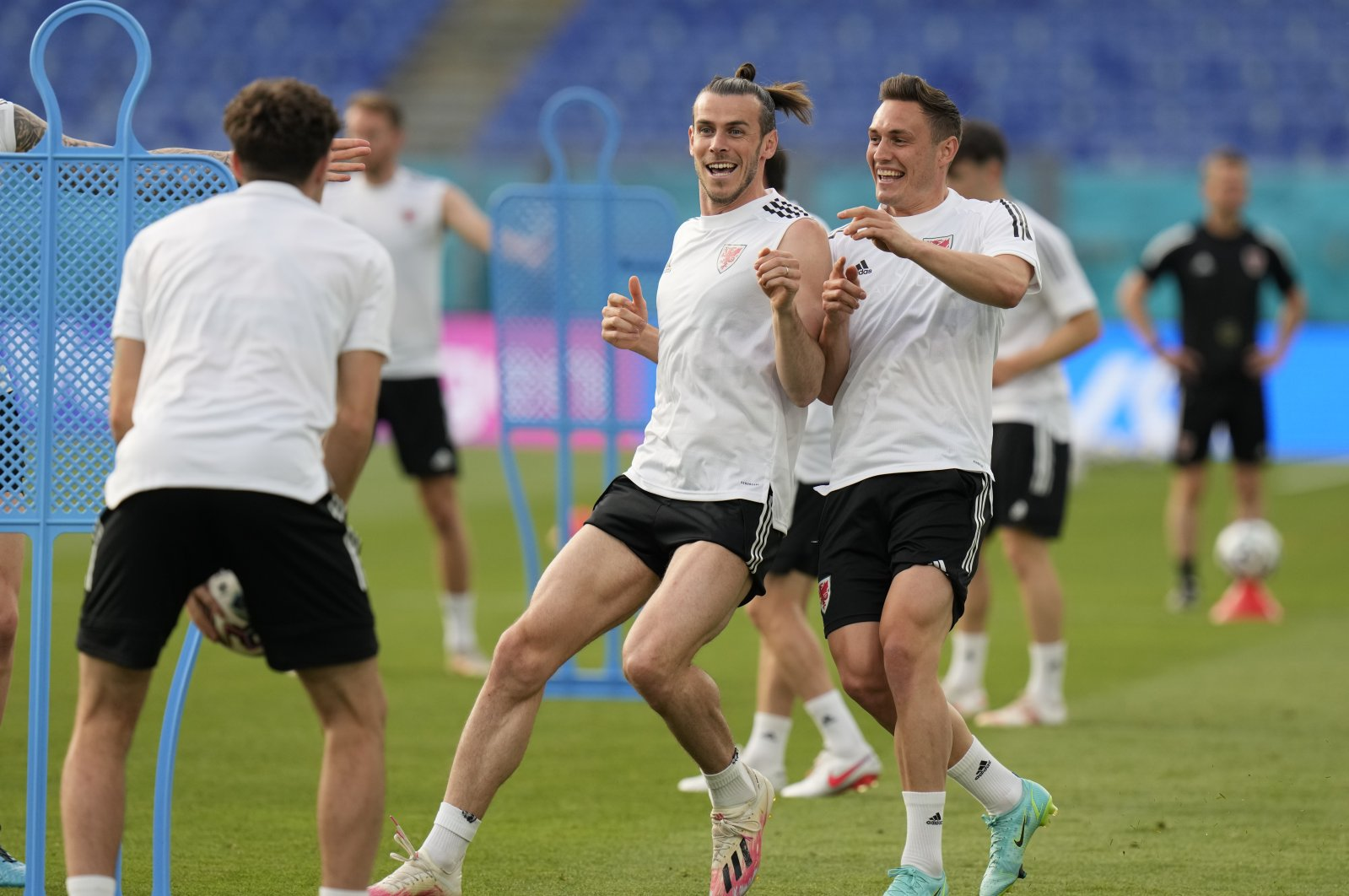 Wales' Gareth Bale (L) and Connor Roberts smile during a team training session at Olympic stadium in Rome, June 19, 2021. (AP Photo)