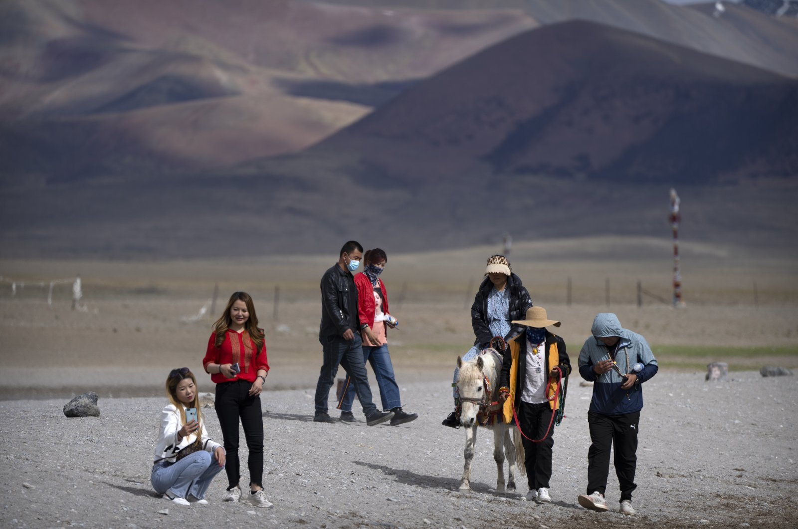 Tourists walk along the lakeshore and ride a pony in Namtso in western China's Tibet Autonomous Region, China, June 2, 2021. (AP Photo)