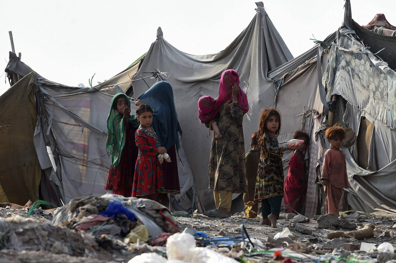 Children of Afghan refugees play outside tents in Afghan Basti area on the outskirts of Lahore on June 19, 2021 on the eve ofWorld Refugee Day. (Photo by Arif ALI / AFP)
