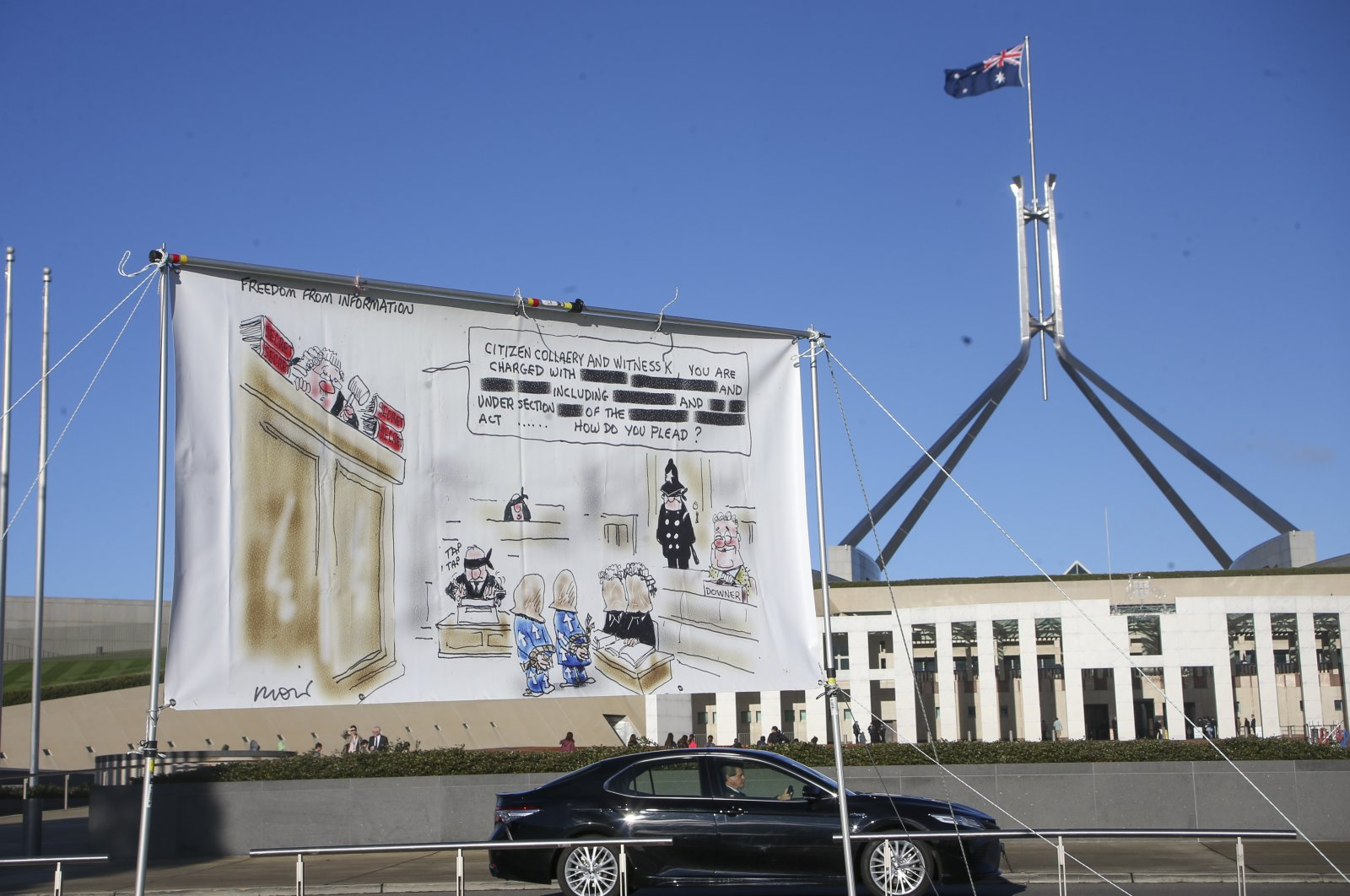 A protest banner hangs outside Parliament House in the Australian capital during a protest against the prosecution of lawyer Bernard Collaery. Critics of the secret prosecutions of a former Australian spy and his lawyer argue they are another example of a government concealing political embarrassment under the guise of national security, June 17, 2021, Canberra, ACT, Australia. (AP Photo)