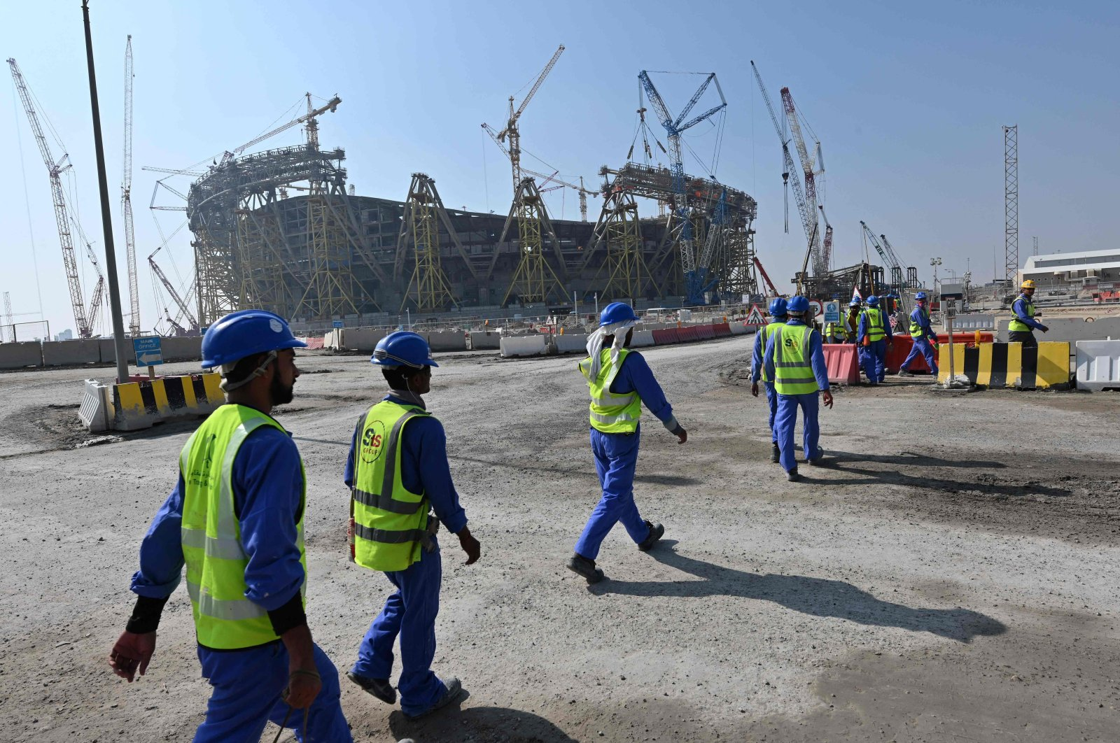 Construction workers walking in front of Qatar's Lusail Stadium while under construction, around 20 kilometers north of the capital Doha, Qatar, on Dec. 20, 2019 (AFP Photo)