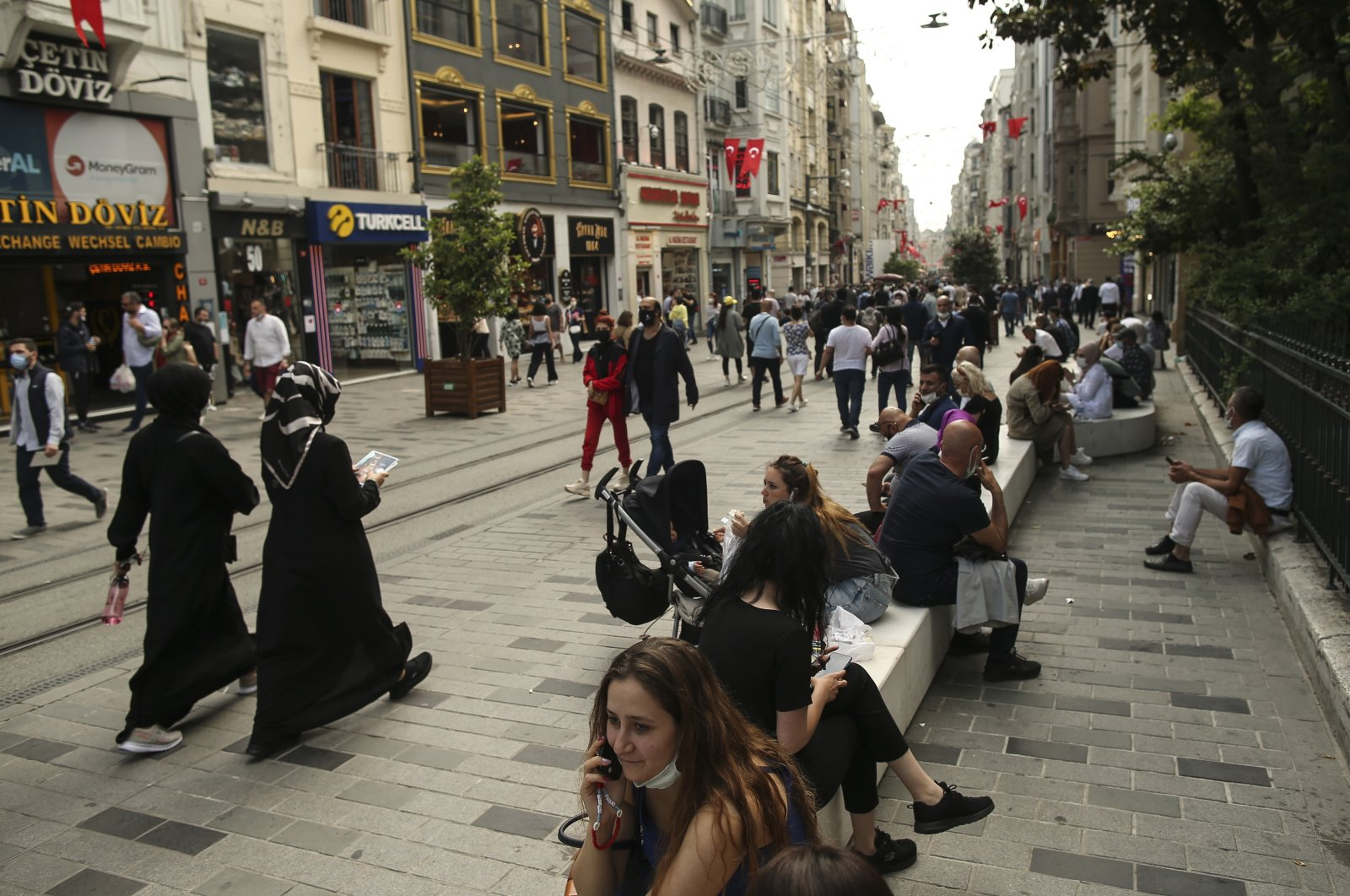 People walk in Istiklal Avenue, the main shopping street of Istanbul, hours before the start of a weekend curfew on May 28, 2021, Istanbul, Turkey. (AP File Photo)