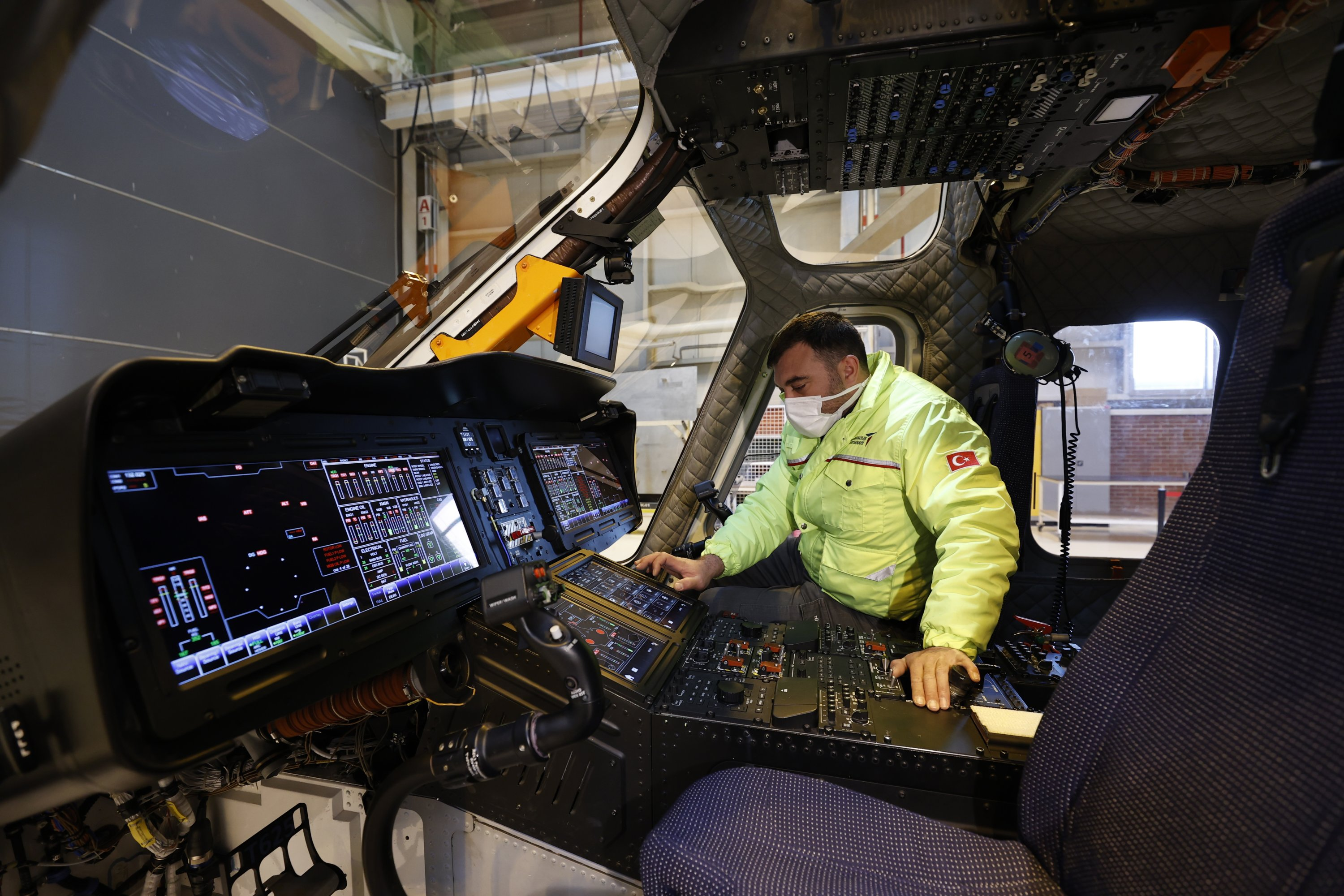 An employee shows the interior parts of the Gökbey multi-role helicopter in the TAI facility, Ankara, Turkey, May 25, 2021. (AA Photo)