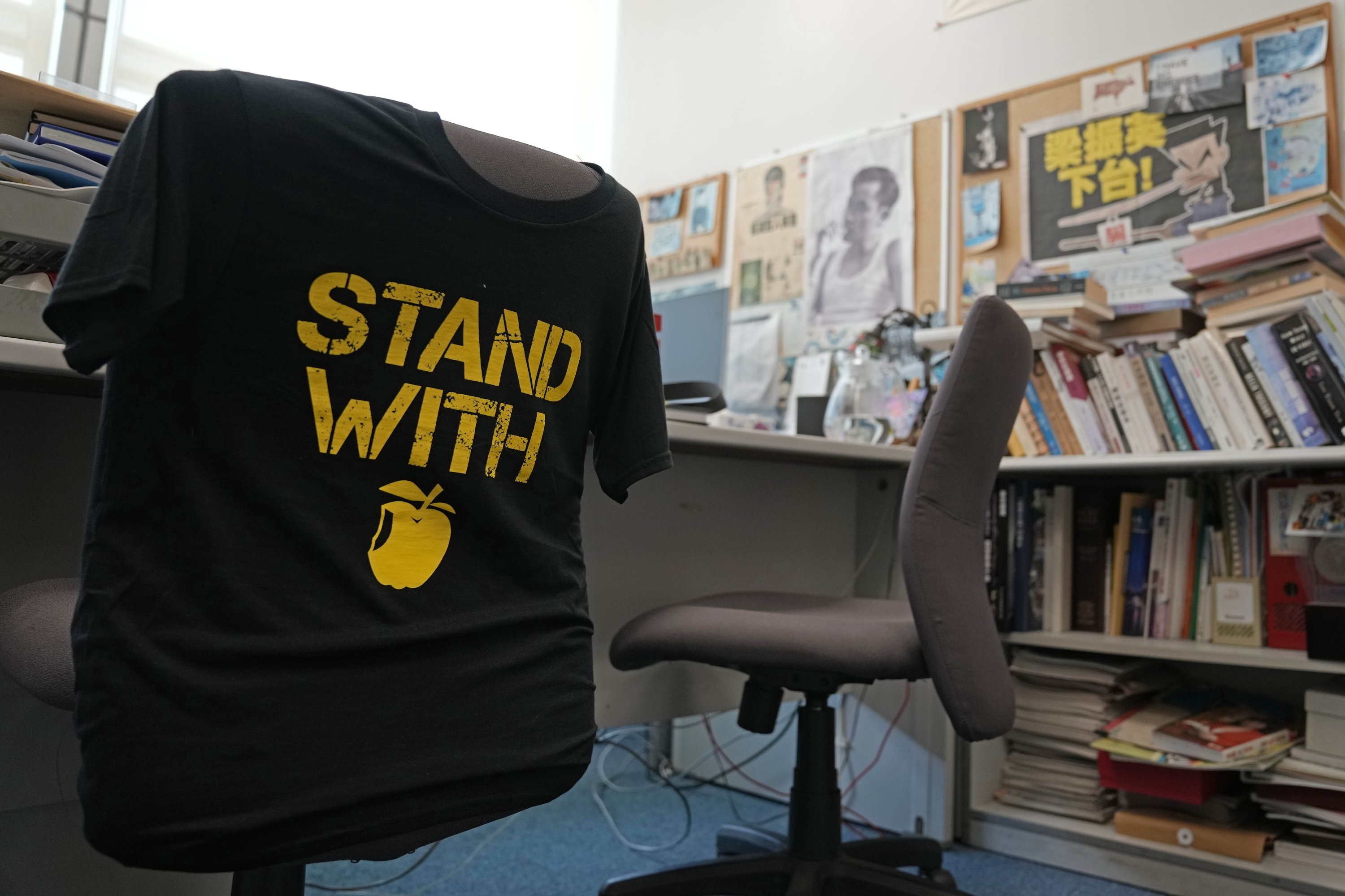 A 'Stand with Apple Daily' t-shirt hangs on a chair in the office of Chan Pui-man, associate publisher of Apple Daily newspaper, at Apple Daily headquarters in Hong Kong, China, June 17, 2021. (AP Photo)