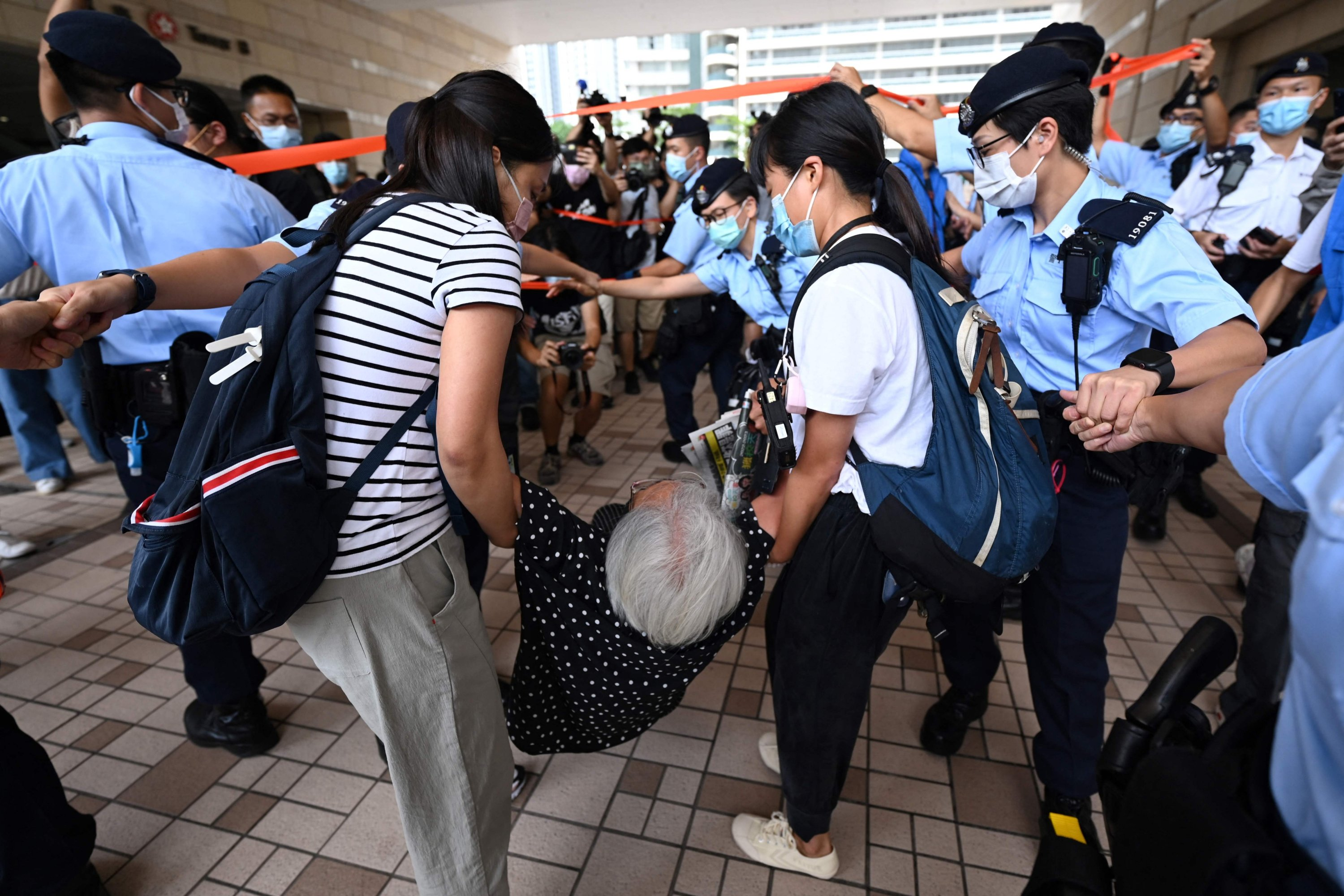 Activist Alexandra Wong (C), also known as Grandma Wong, is dragged away by police inside the court grounds in Hong Kong, China, June 19, 2021. (Photo by AFP)