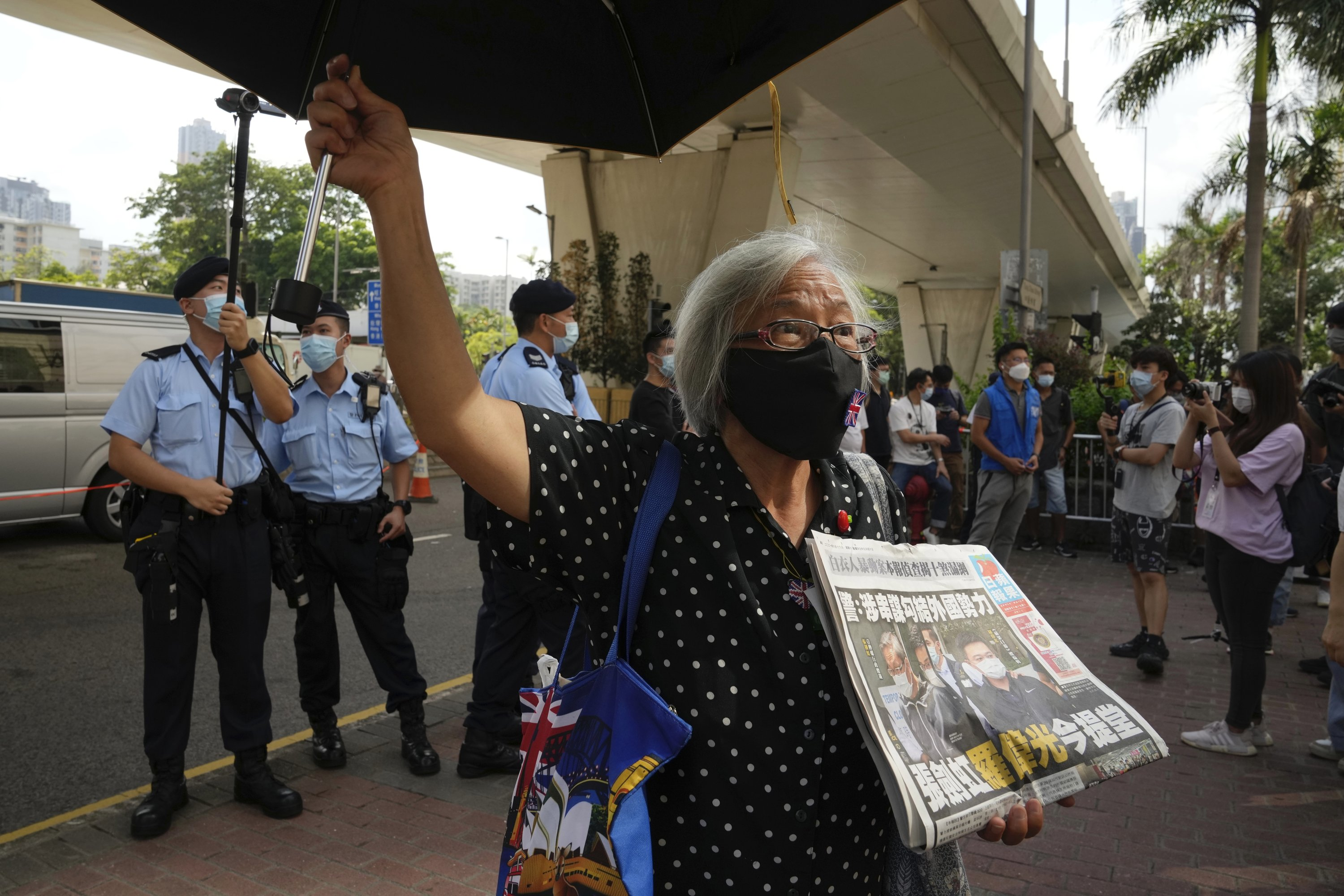 Activist Alexandra Wong, also known as Grandma Wong, holds a copy of the Apple Daily newspaper during a protest outside a court in Hong Kong, China, June 19, 2021. (AP Photo)