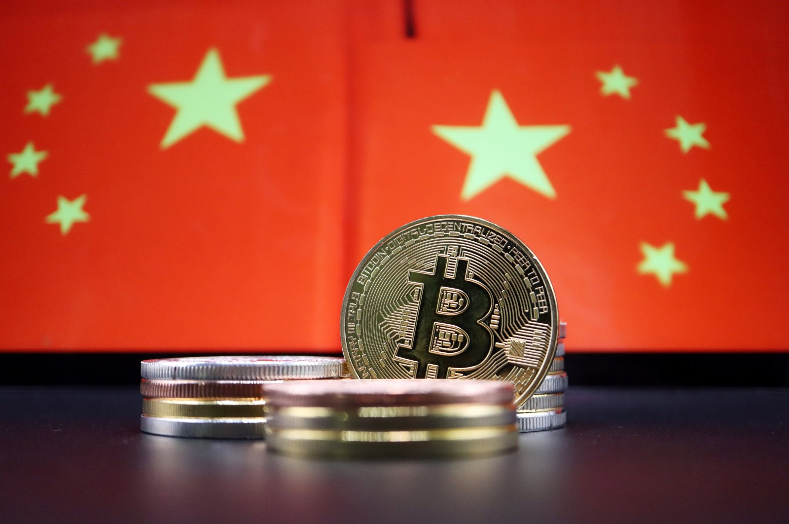 Representations of Bitcoin are seen in front of an image of Chinese flags in this illustration picture taken June 2, 2021. (Reuters Photo)