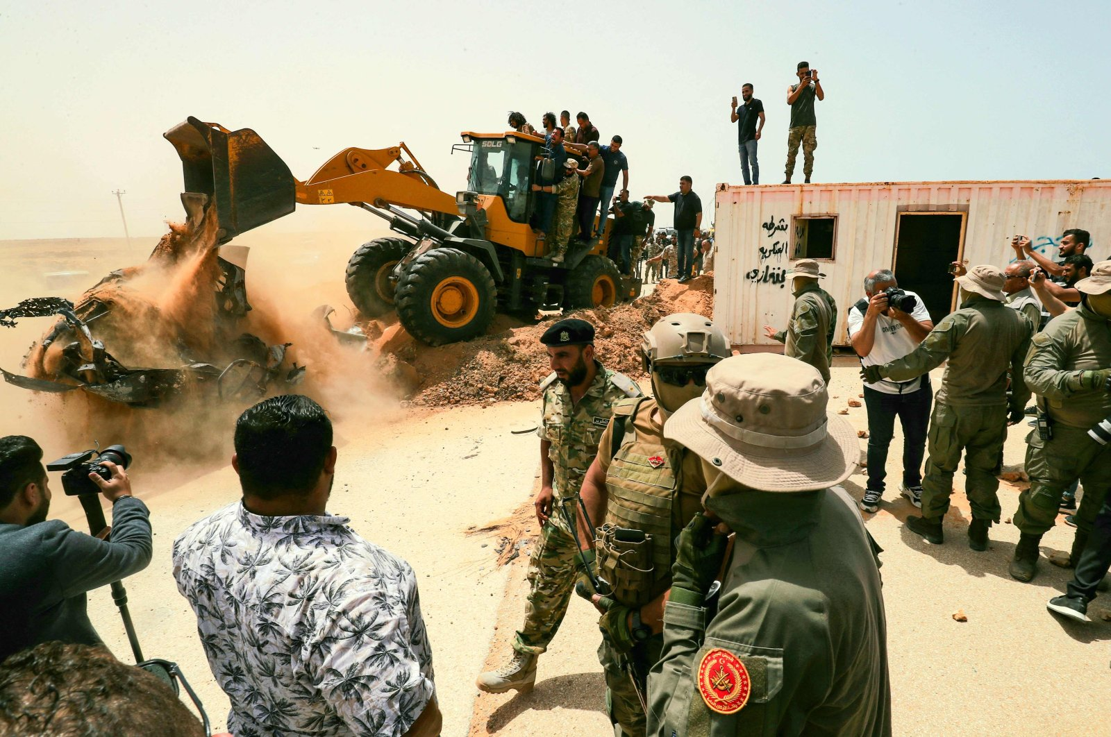 People cheer as an excavator removes rubble during a ceremony marking the reopening of a road between the cities of Misrata and Sirte, in the town of Buwairat al-Hassoun, Libya, June 20, 2021. (AFP Photo)