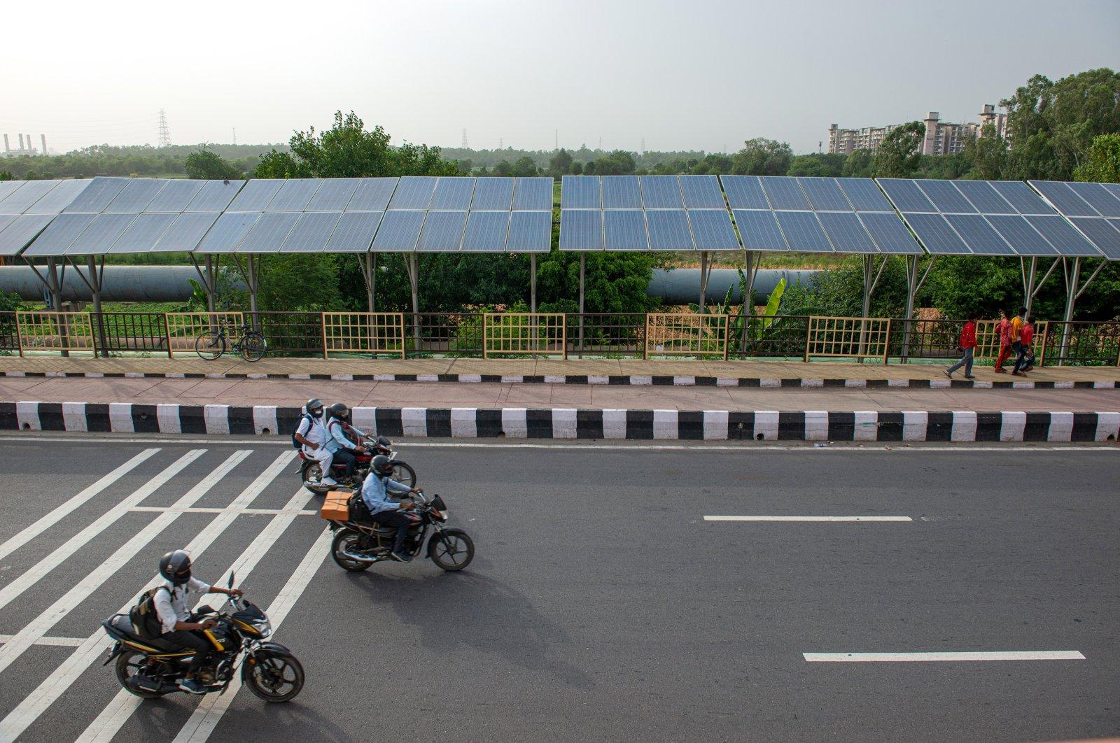 Bikers pass near solar panels installed on Delhi Meerut expressway, New Delhi, India, June 15, 2021. (Shutterstock Photo)