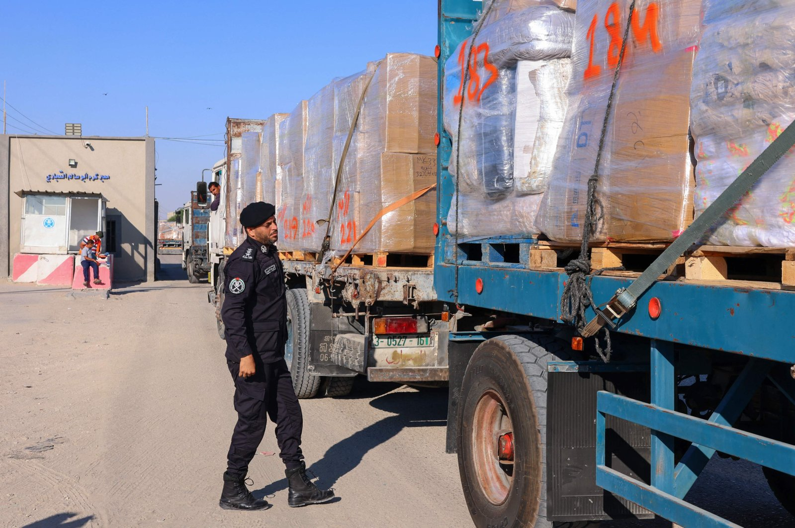 A Palestinian police officer searches a truck's fabrics cargo slated for export at Kerem Shalom crossing in Rafah in the southern Gaza Strip, Palestine, June 21, 2021. (AFP Photo)