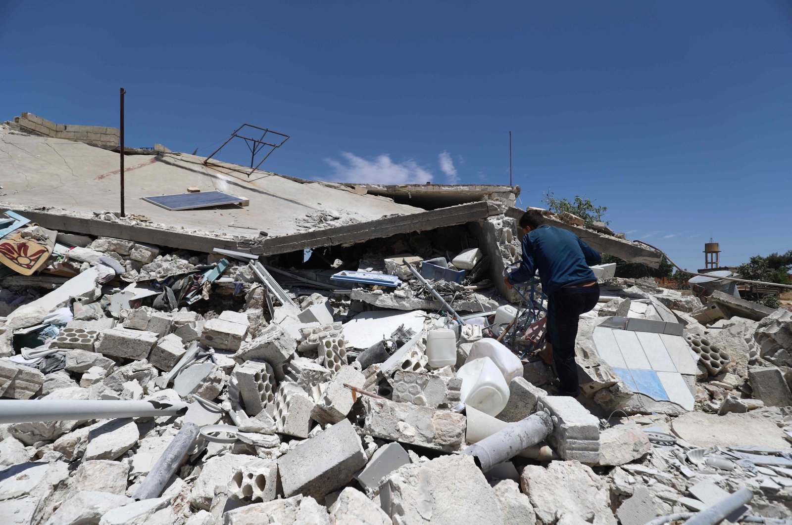 A man looks through the rubble of a destroyed house in the village of Iblin in the Jabal al-Zawiya region in Syria's opposition-held northwestern Idlib province, June 10, 2021. (AFP Photo)