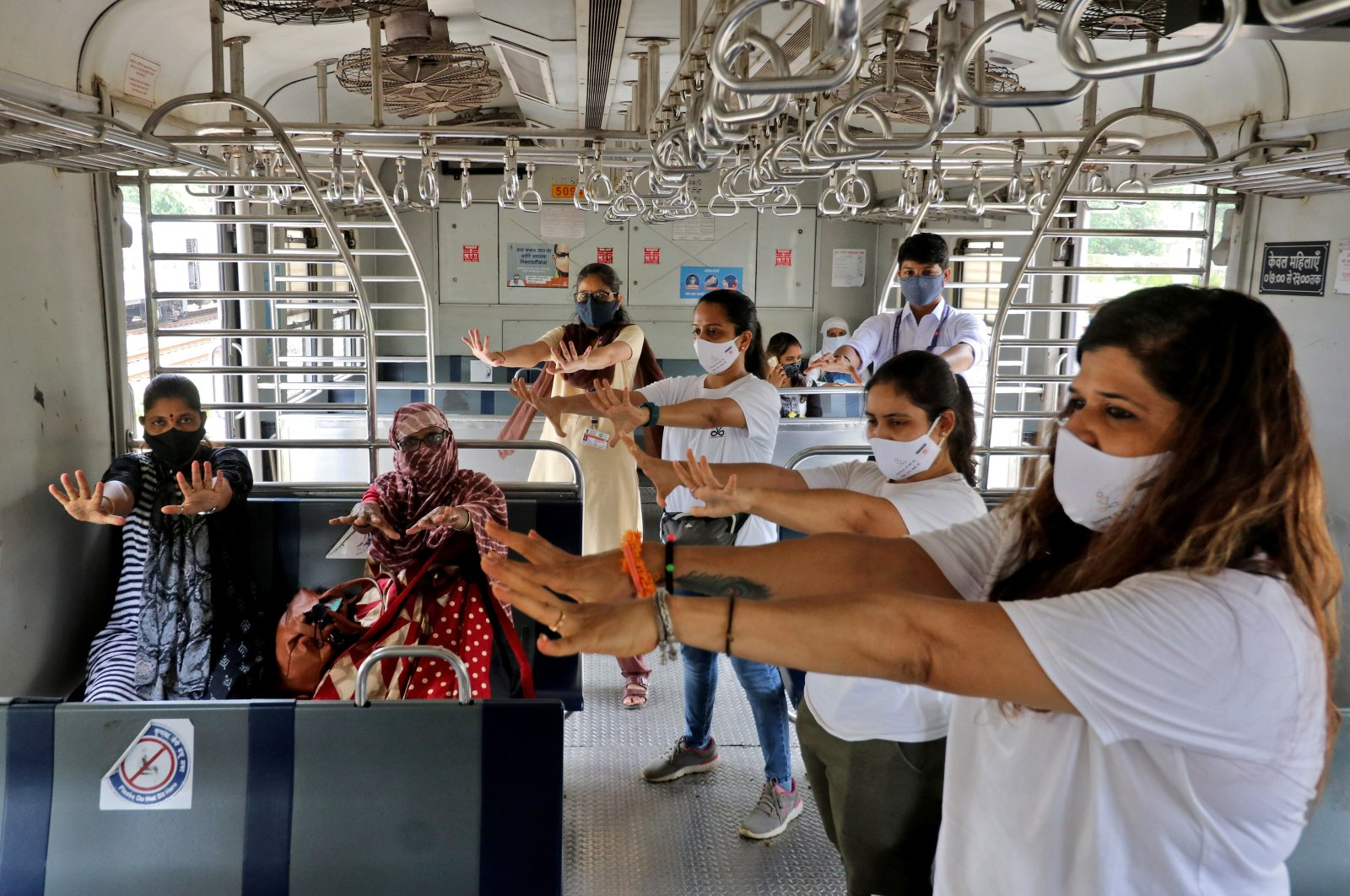 Women perform yoga in a local train on the occasion of International Yoga Day, amid the ongoing COVID-19 pandemic, in Mumbai, India, June 21, 2021. (Reuters Photo)