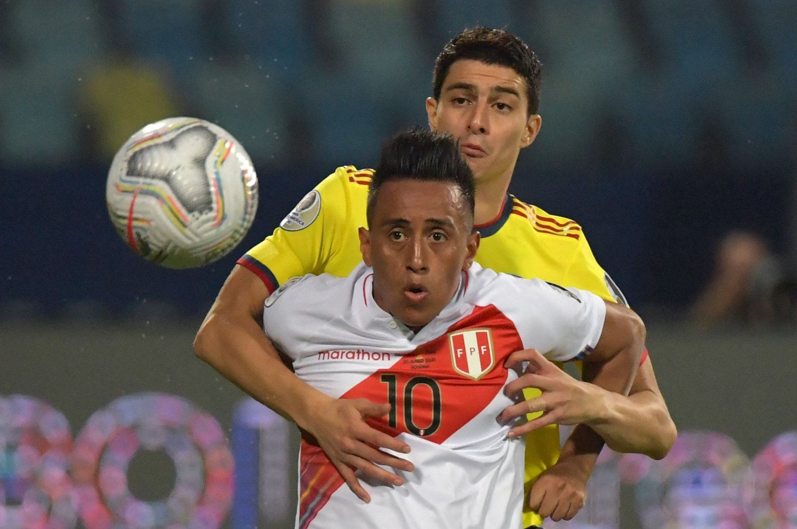 Peru's Christian Cueva (Front) and Colombia's John Medina vie for the ball during their Copa America 2021 group match at the Olympic Stadium in Goiania, Brazil, June 20, 2021. (AFP Photo)